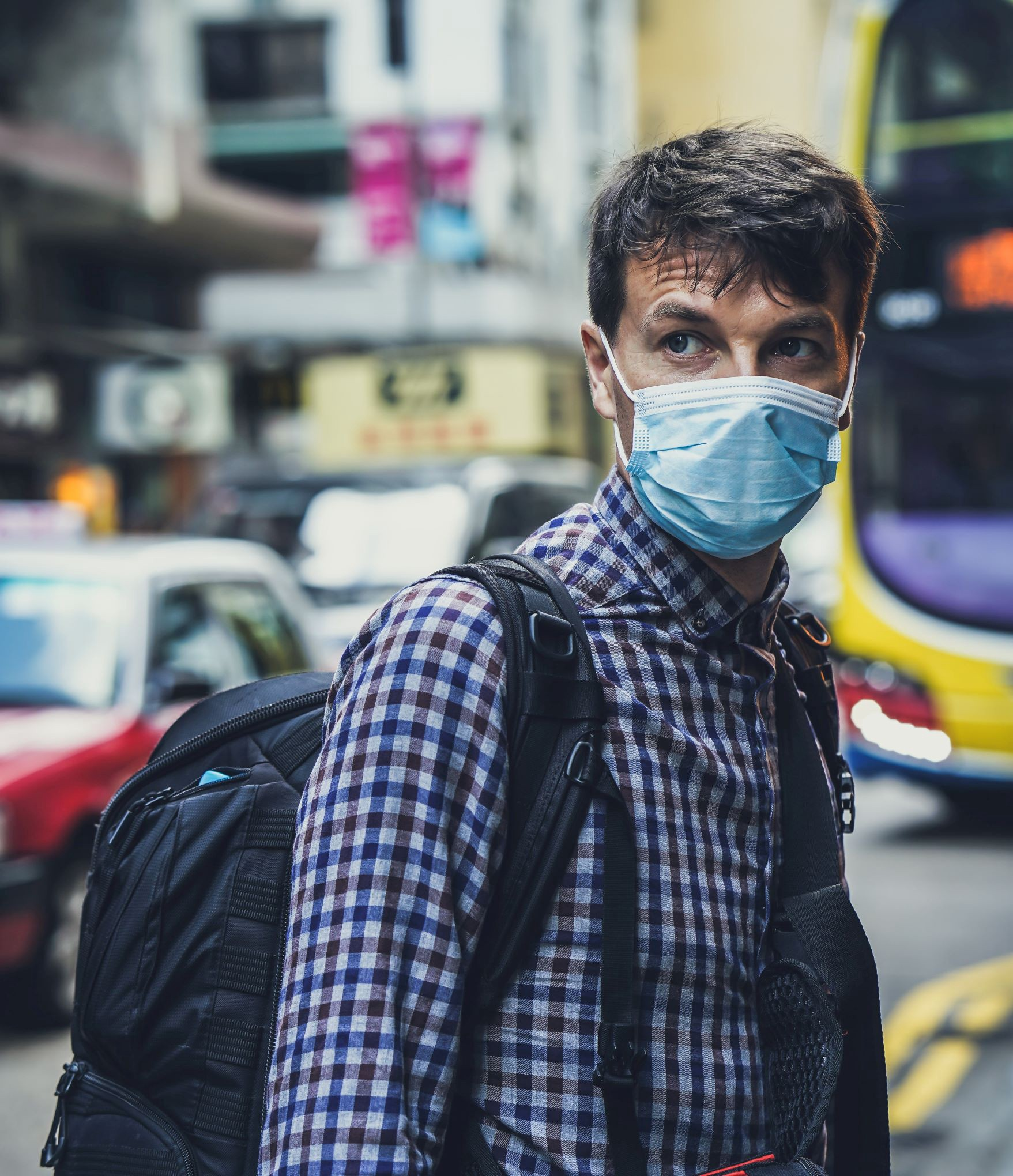 Young man traveling wearing medical mask