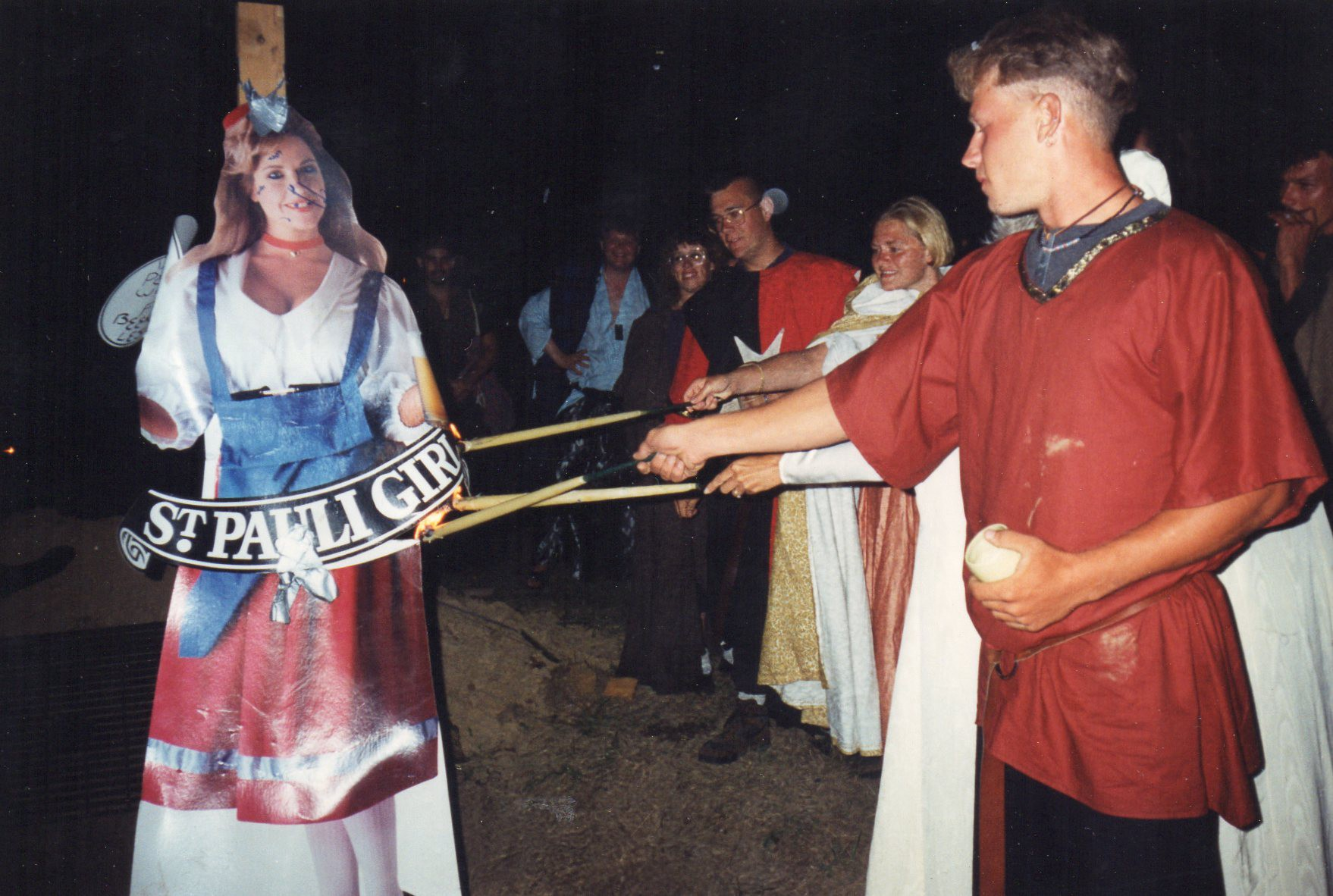 Old 1993 photograph at a party of people dressed in medieval clothes burning a St. Pauli Girl standout at a party
