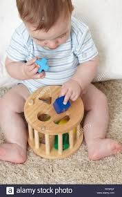 Child trying to fit blocks into appropriately shaped holes.