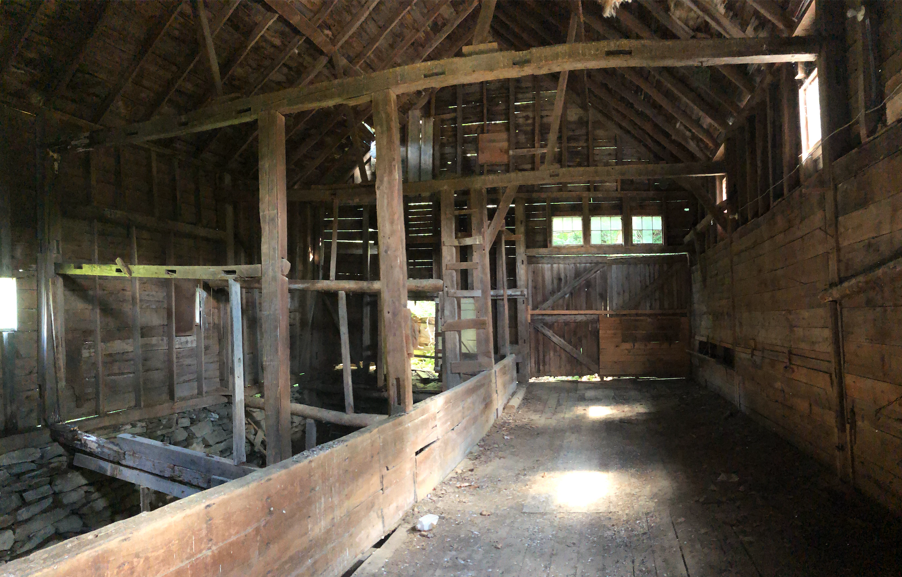 A cathedral-height barn made of wood, in disrepair, shot through with sunbeams,