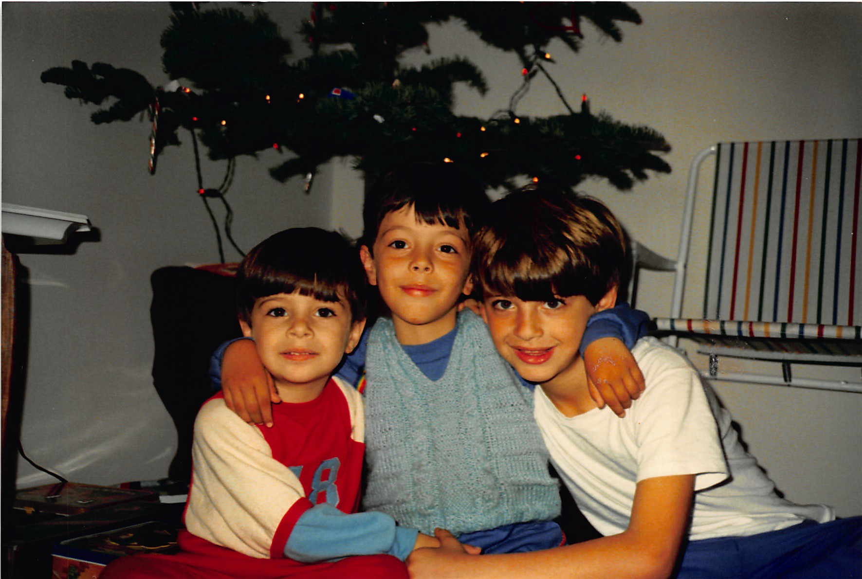 Three boys sit in front a sparely decorated Christmas Tree. The middle boy supports himself on the shoulders of the other two