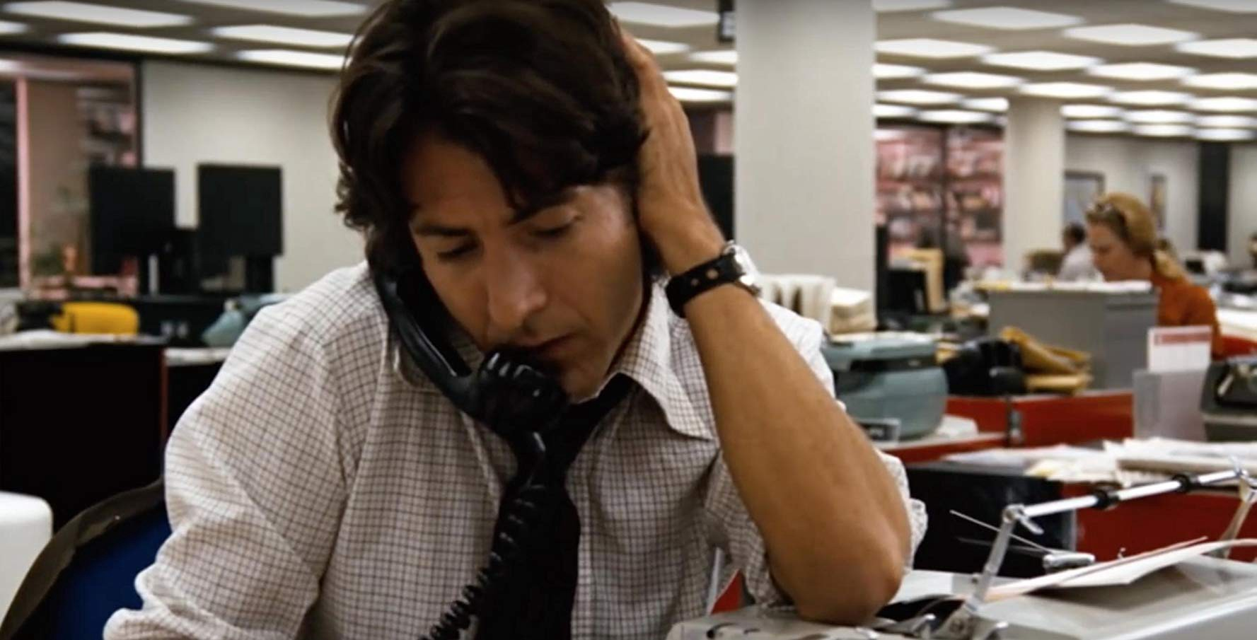 Still from the movie All the President's Men. Dustin Hoffman on the telephone in a newsroom with his hand over his ear.