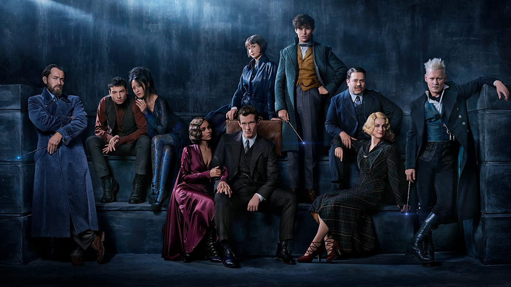 The cast of Fantastic Beasts 2 dressed as their characters in front of a blue dark background.