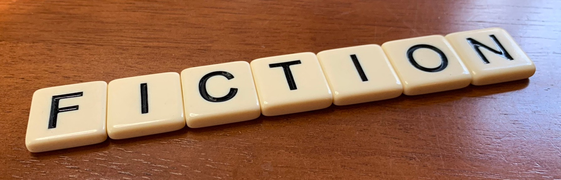 "Letter tiles spelling out ""Fiction"" on a wooden desktop"