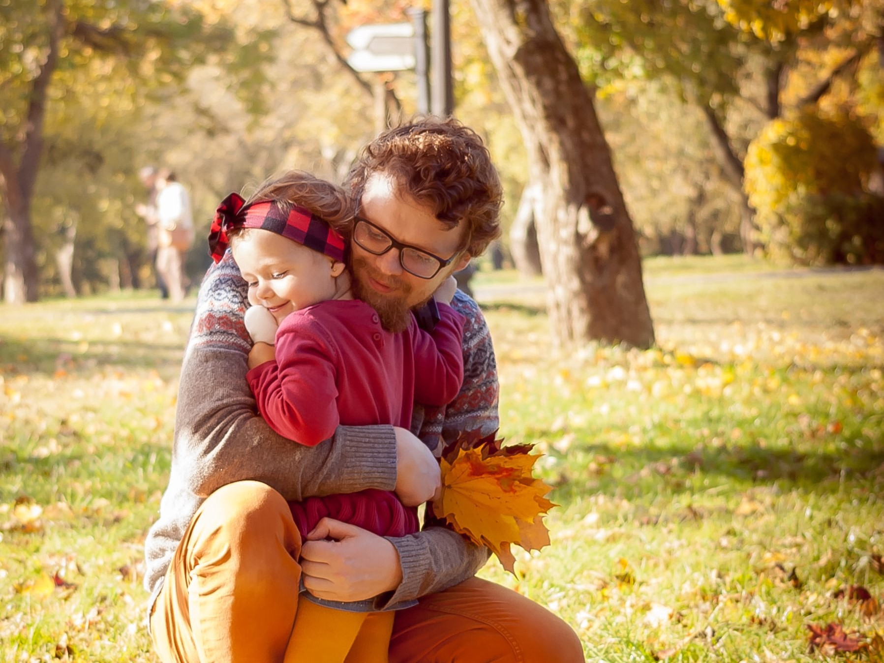 Dad lovingly hugs his toddler in a park, surrounded by autumn leaves