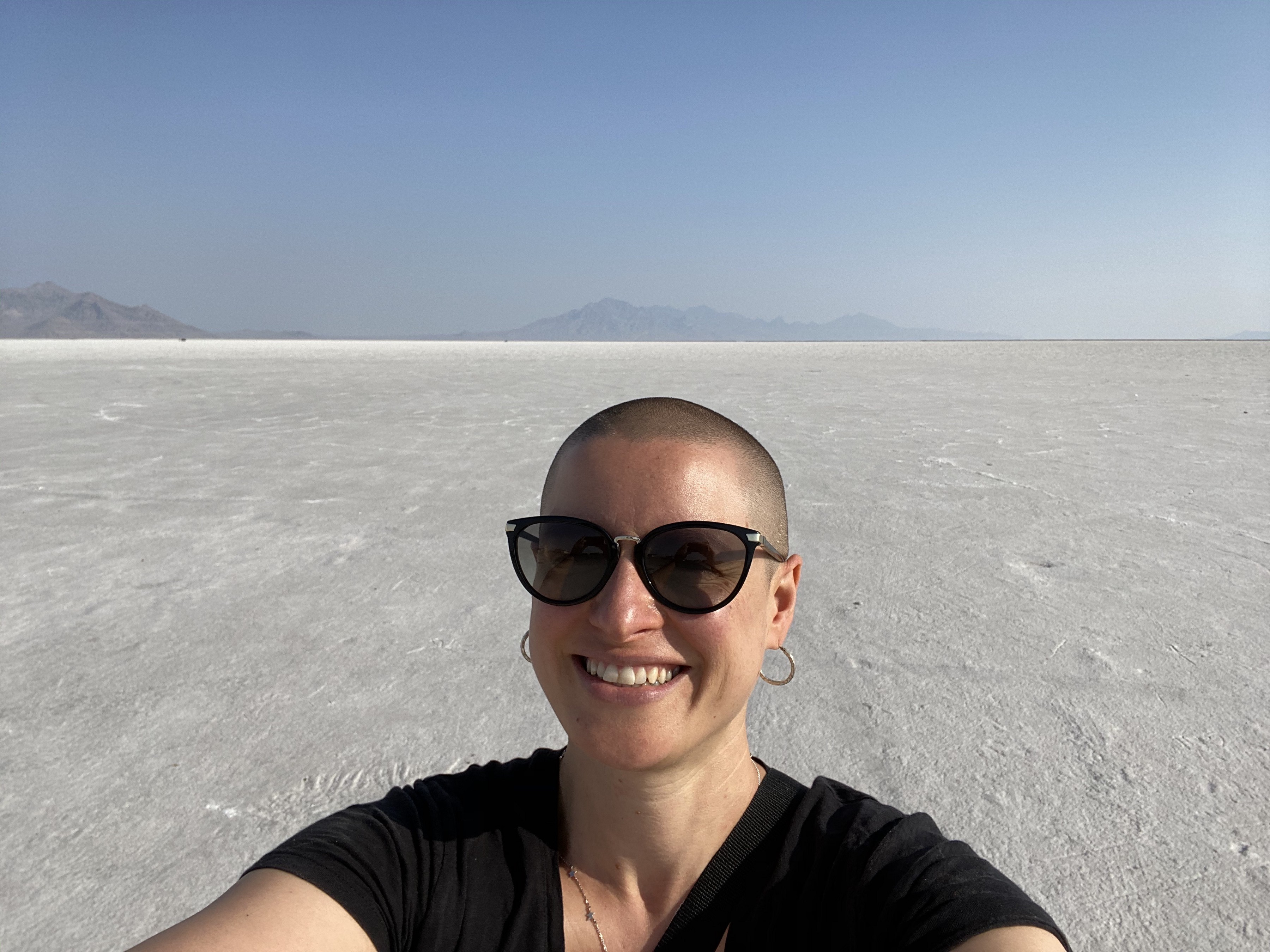 Sarah Dopp smiling with a large stretch of salt flats in the background. She is white, has shaved head, wearing sunglasses.