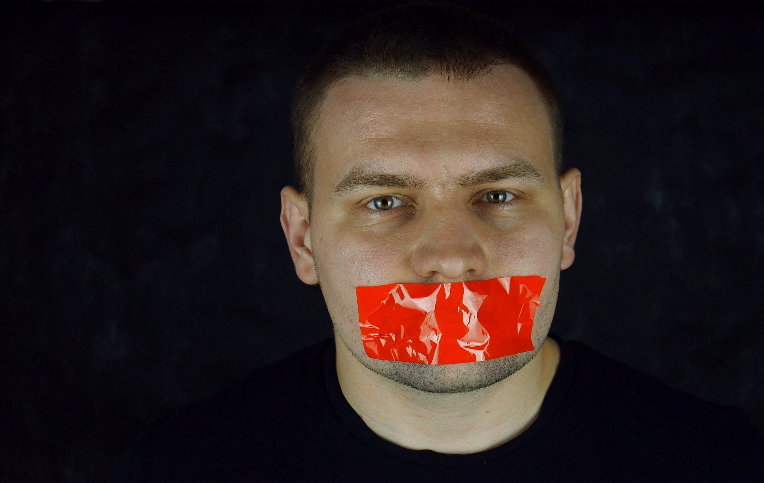 Man with red tape over his mouth
