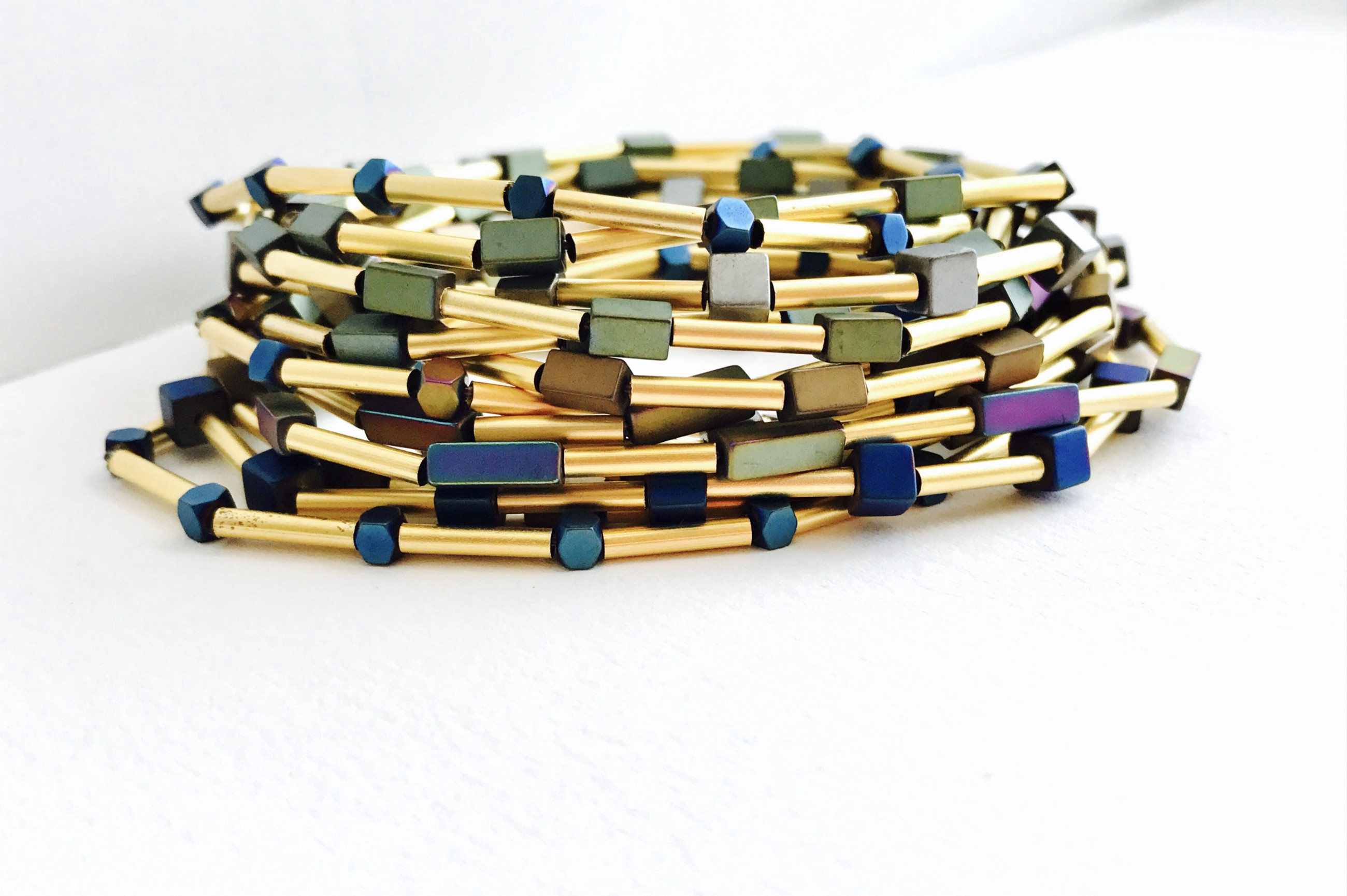 stack of bracelets made with gold cylindrical beads and colored beads.