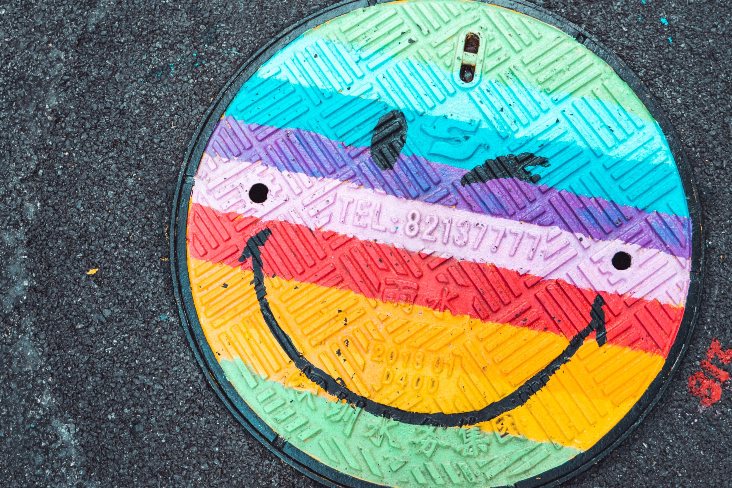 Smily face on a manhole cover, but painted in a pastel rainbow.