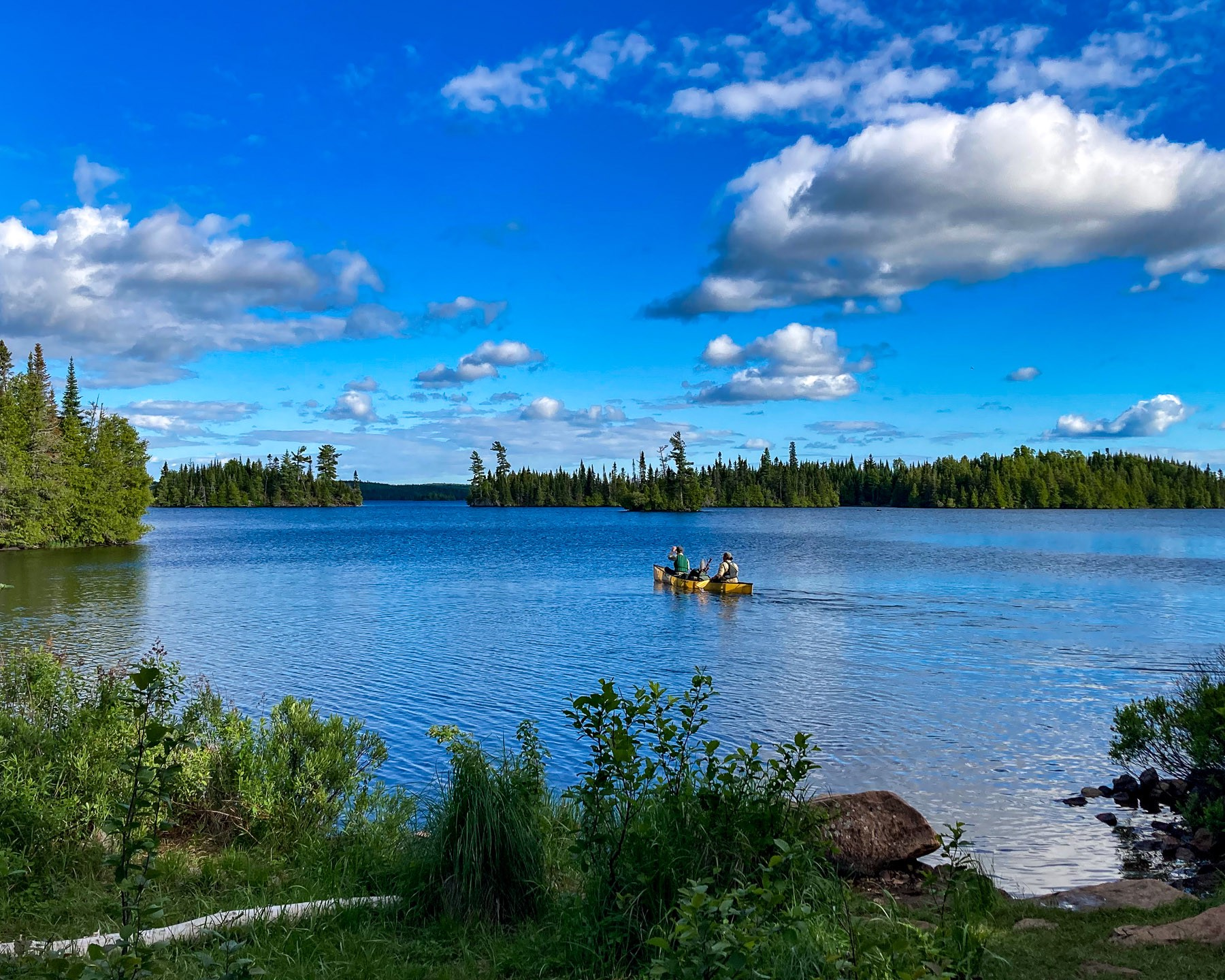 Rangers paddle away from our camp on Brule Lake. Photo courtesy of Nick Runtsch.