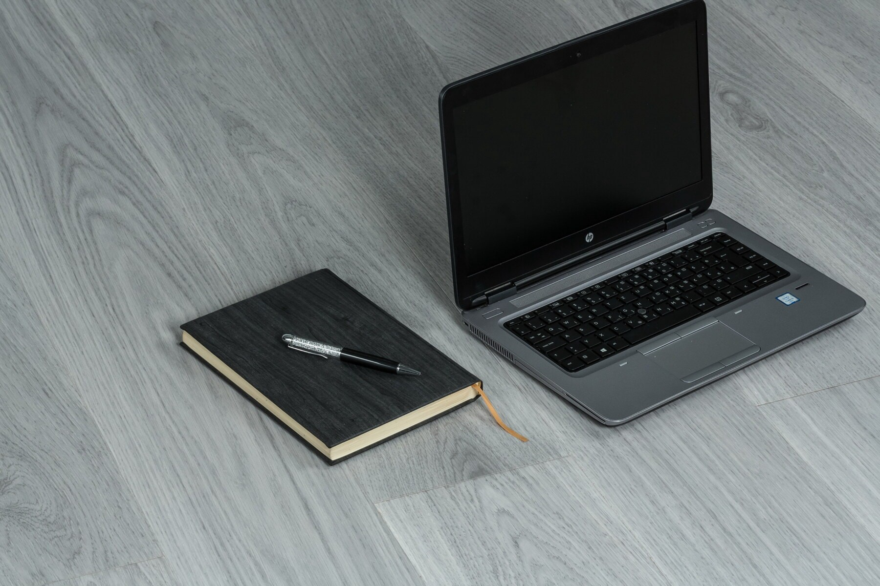A computer and a notebook on grey table.