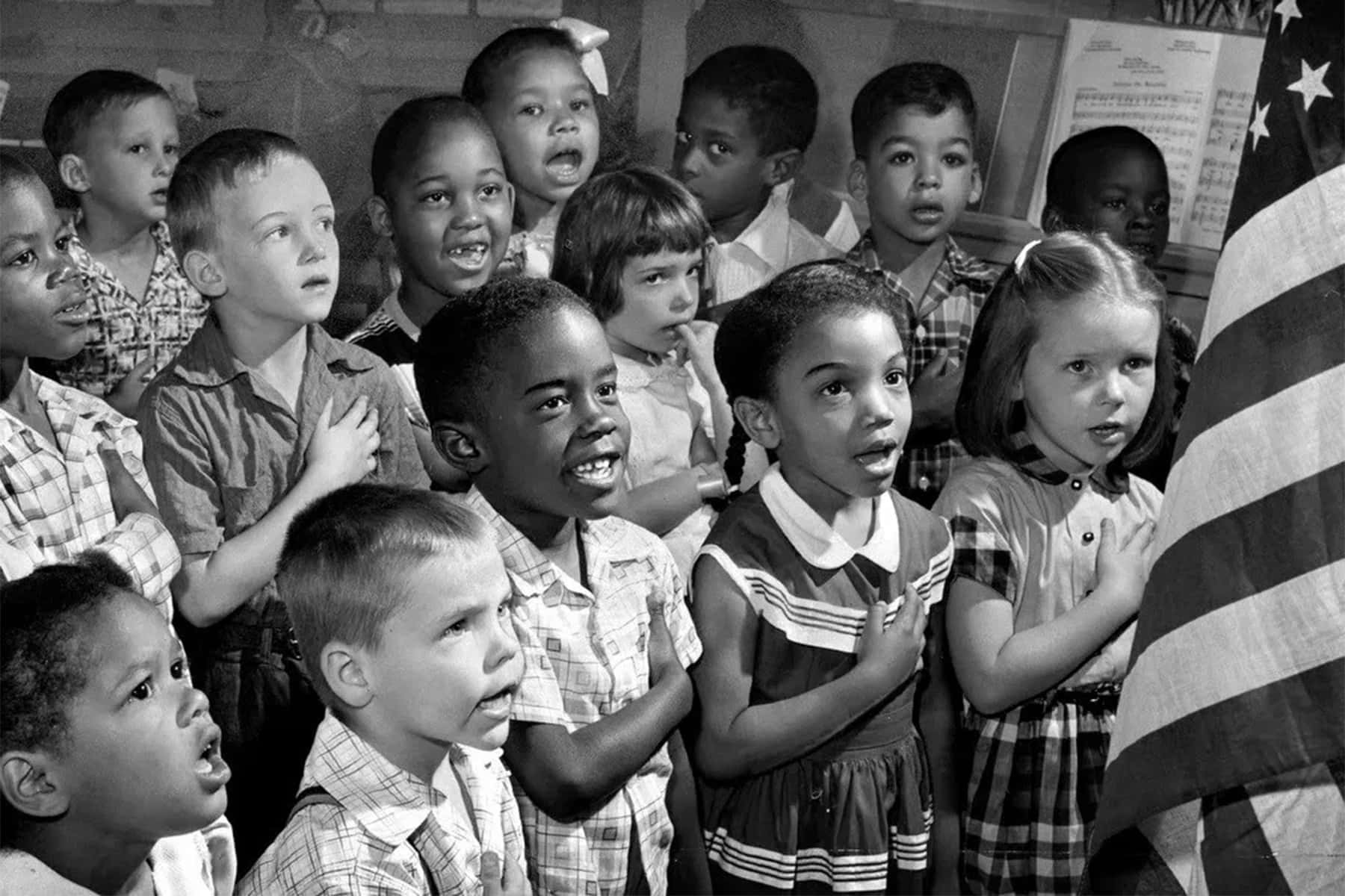 Children saying the Pledge of Allegiance in front of an American flag.