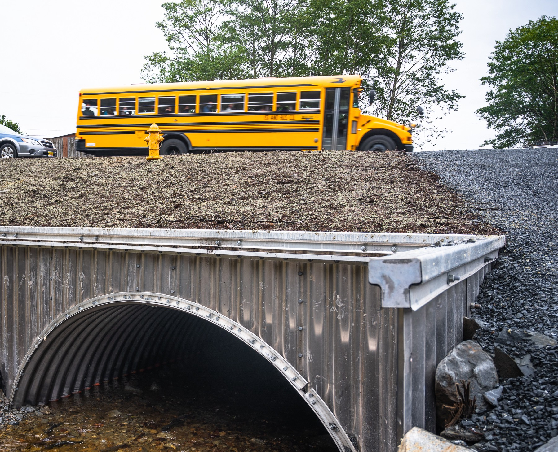 a bus drives over an arched culvert through which a salmon stream passes