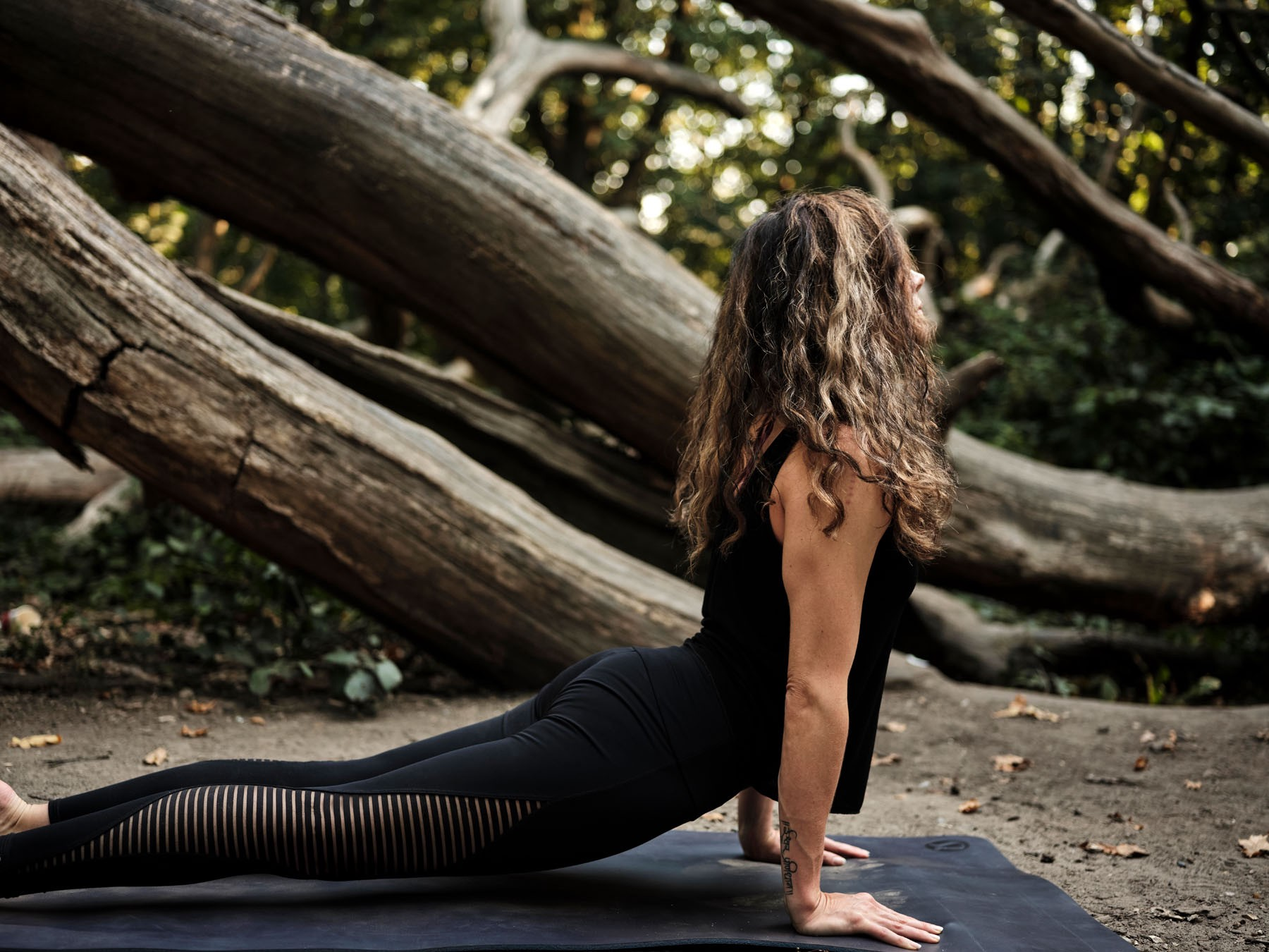 Woman in yoga pose in woods