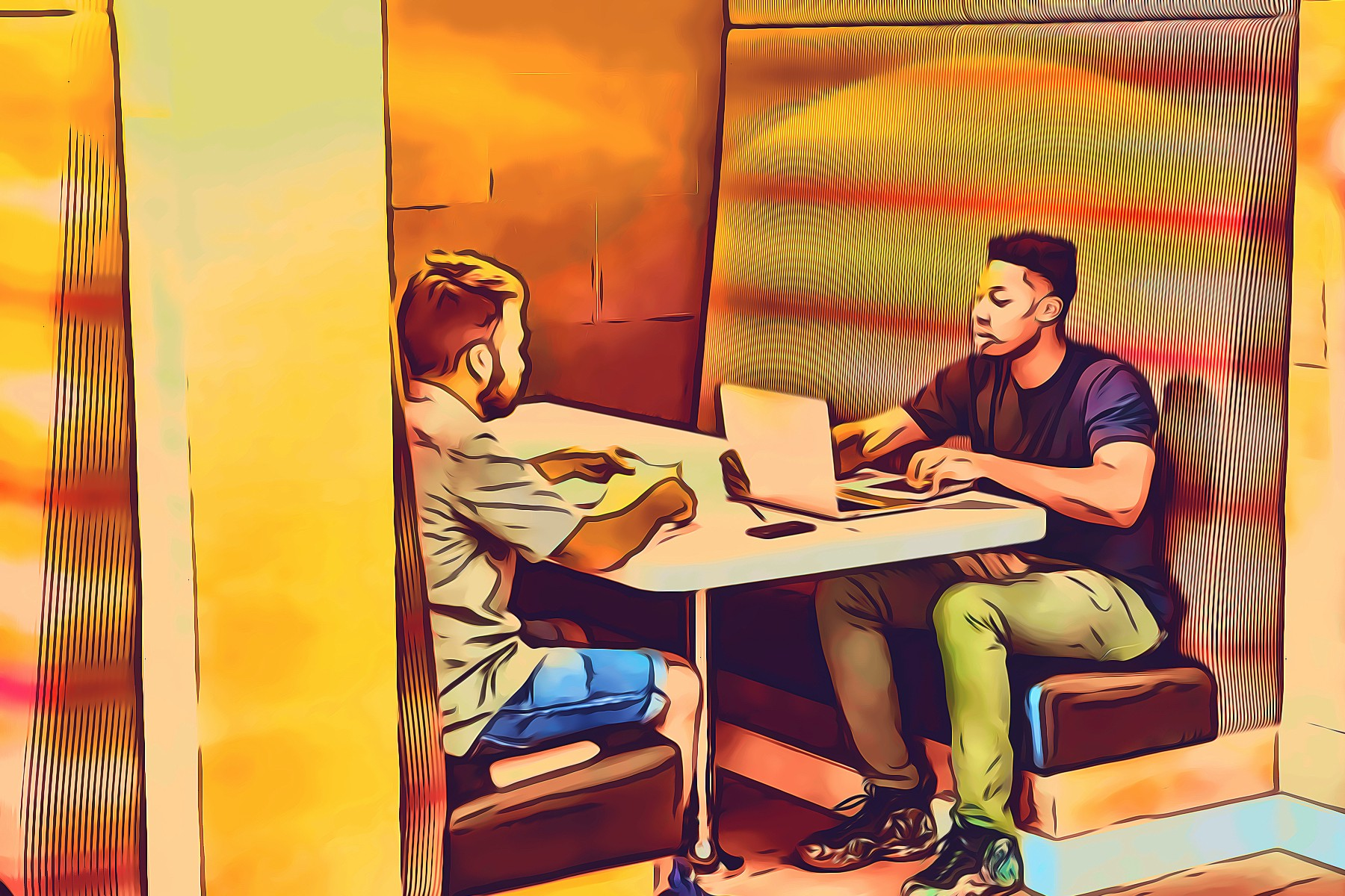 Two men sitting in a booth with a laptop, talking