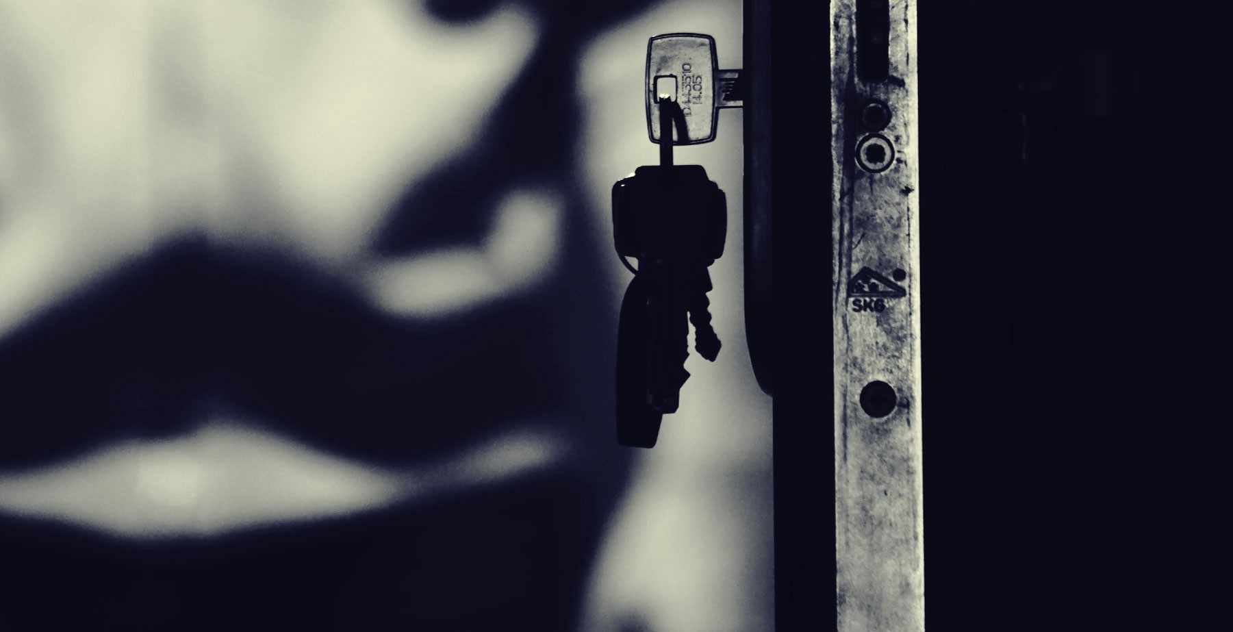 dark door with keys hanging from the lock a shadowy figure in the back