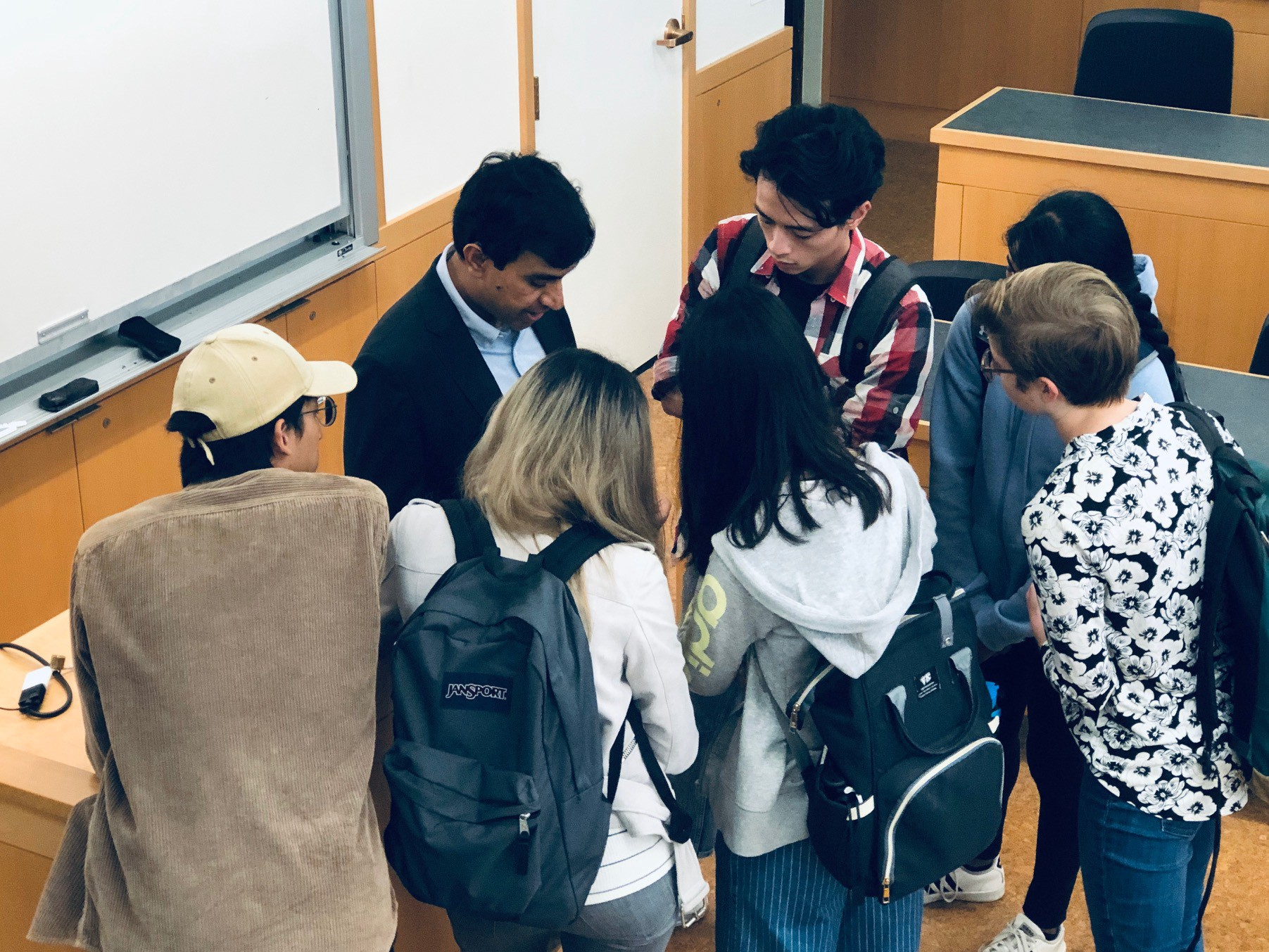 Atchin with a group of MEng students surrounding him in conversation.