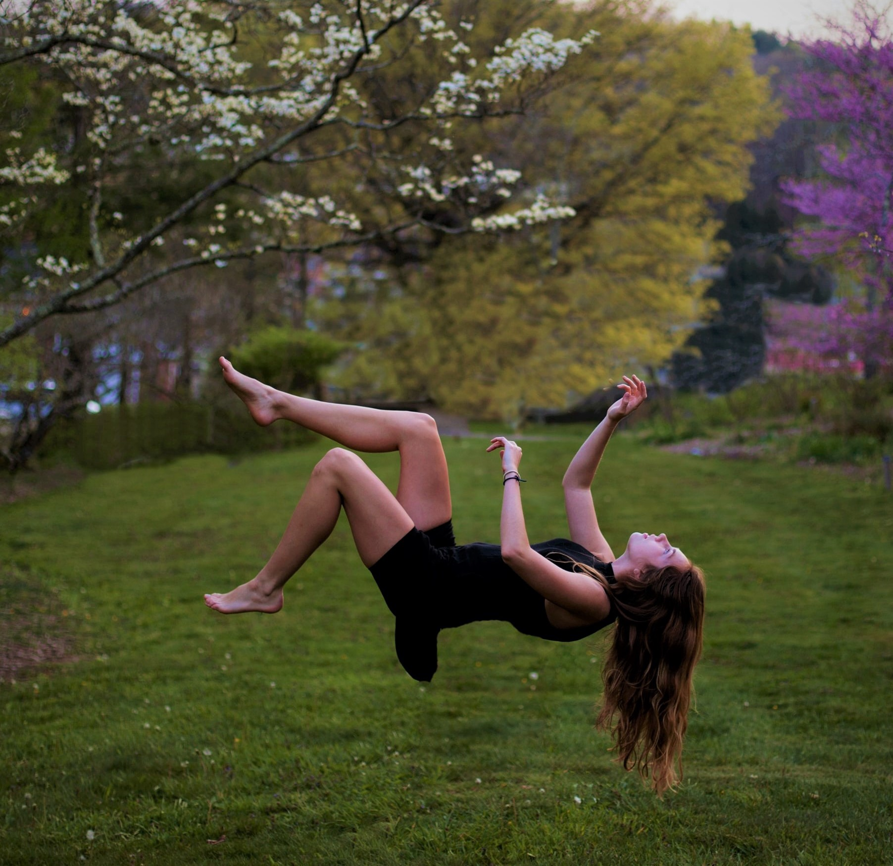 girl with long dark hair wearing black dress floating in air above grassy lawn
