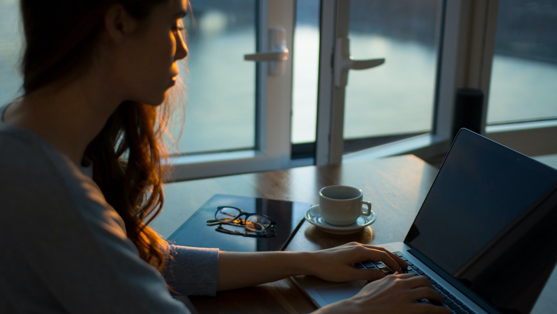 Woman in shadow in front of laptop