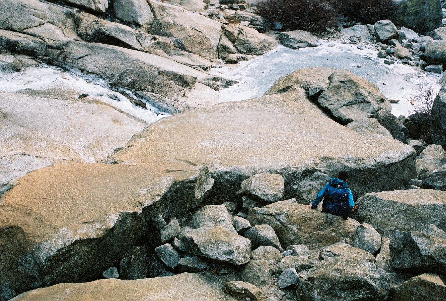 Me, climbing down some boulders, towards a frozen river.