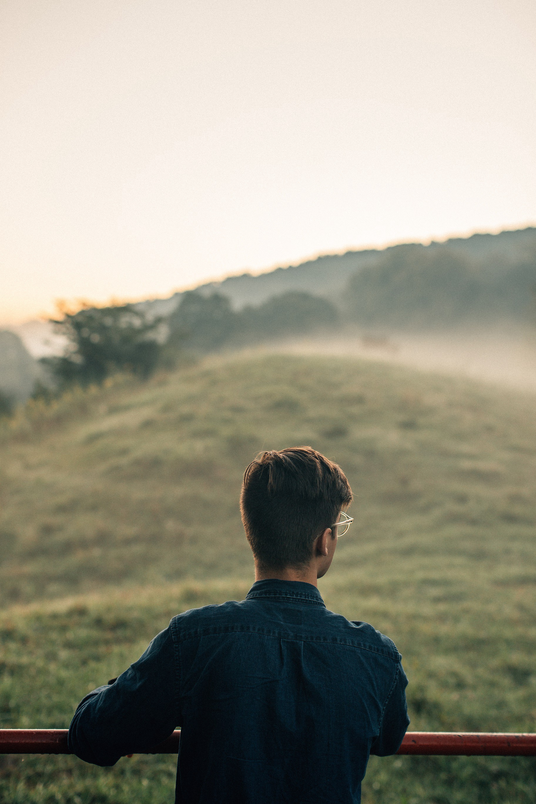 Man looking at a foggy hill.