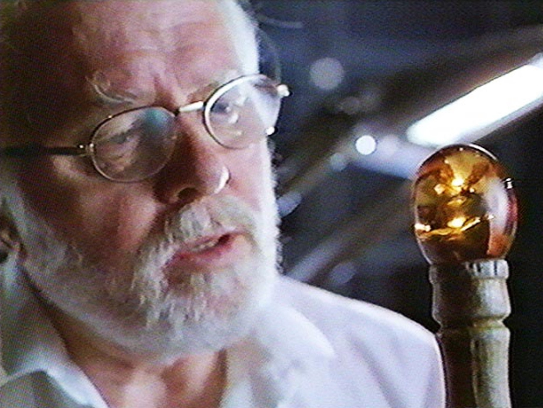 Jurassic Park owner, Hammond, inspects mosquito in amber that is part of his walking stick