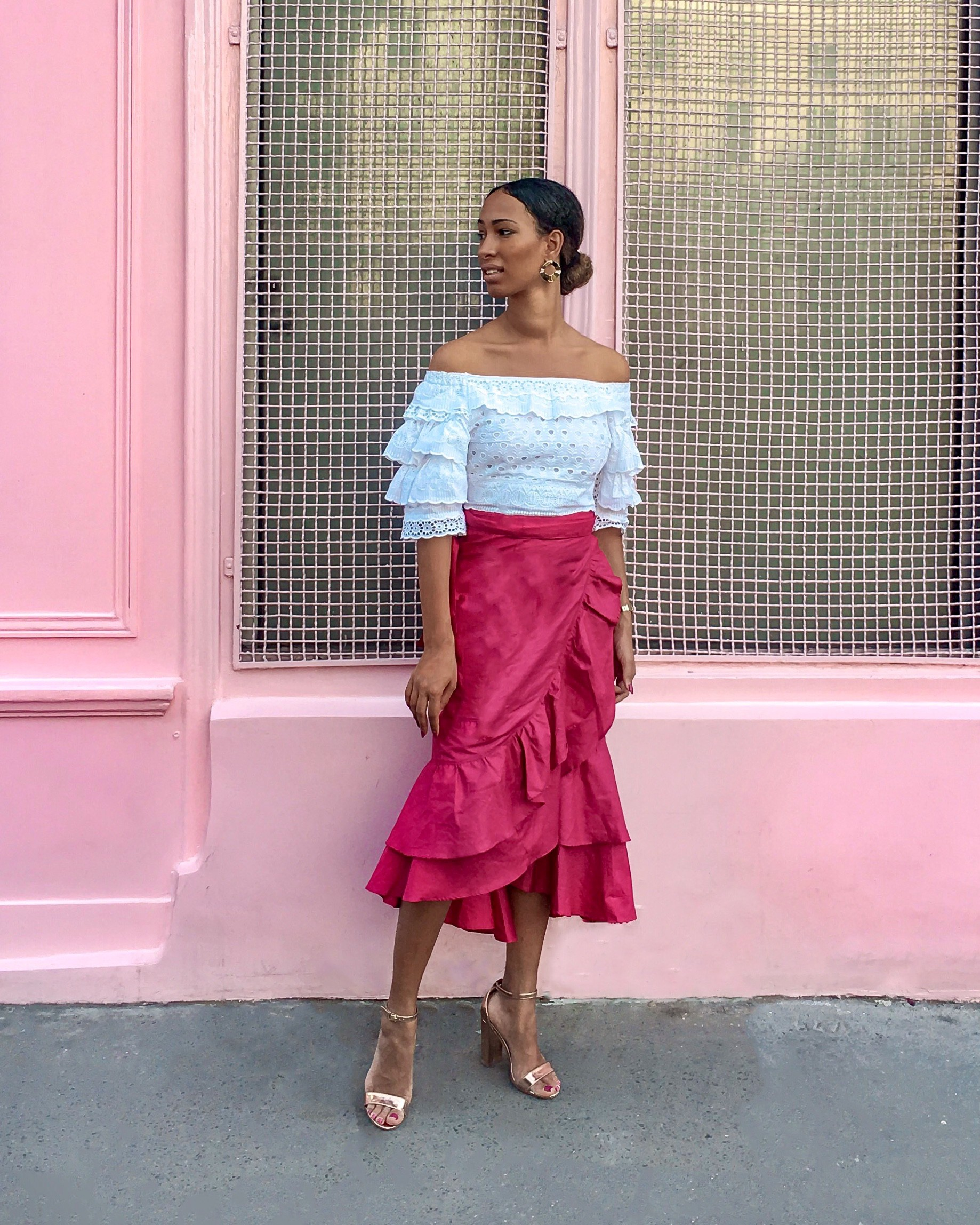 Woman wearing pink skirt with ruffles and white crop top