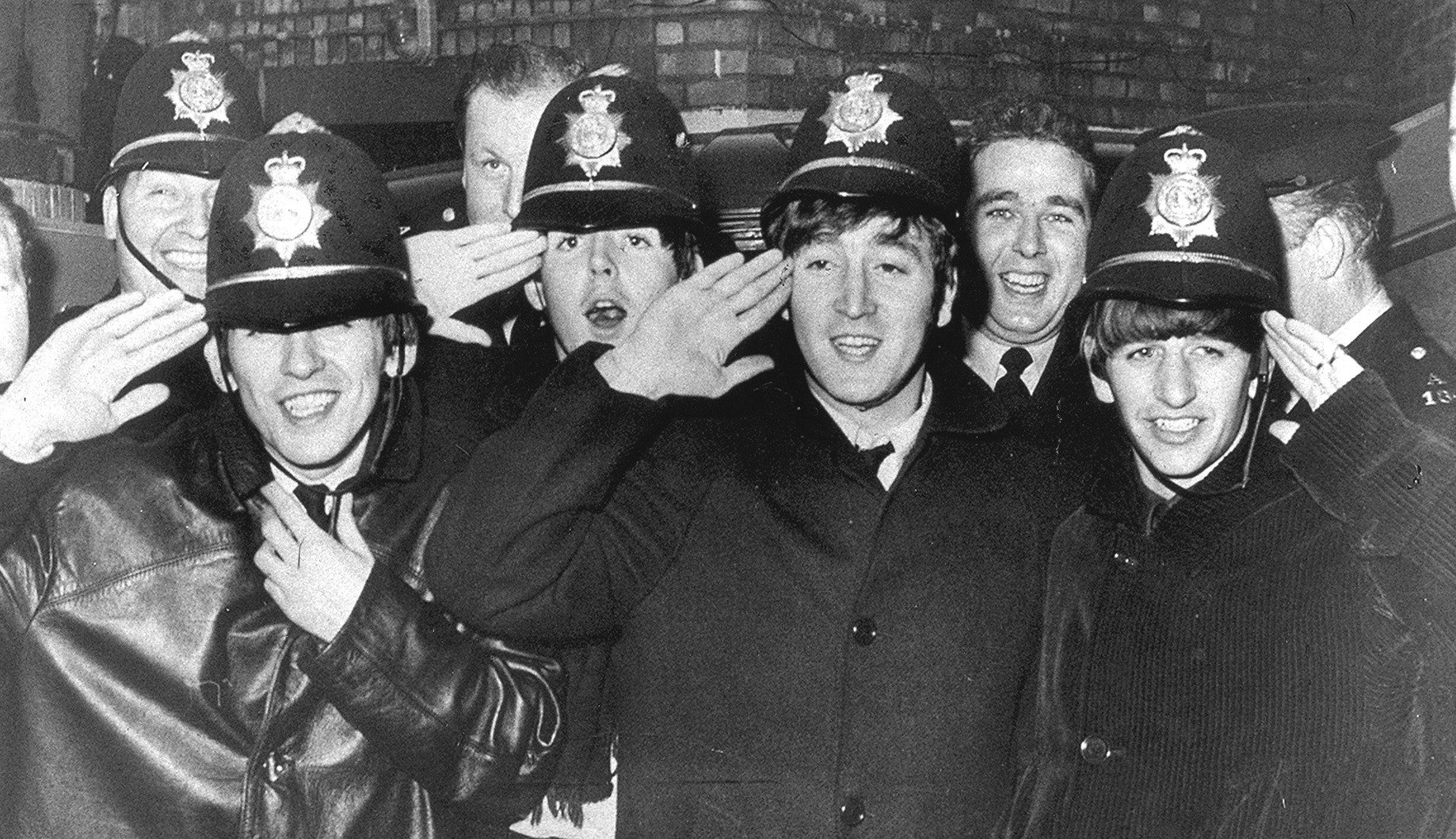 Photograph of The Beatles pop group dressed in British police uniform in 1963 at a concert in Birmingham UK