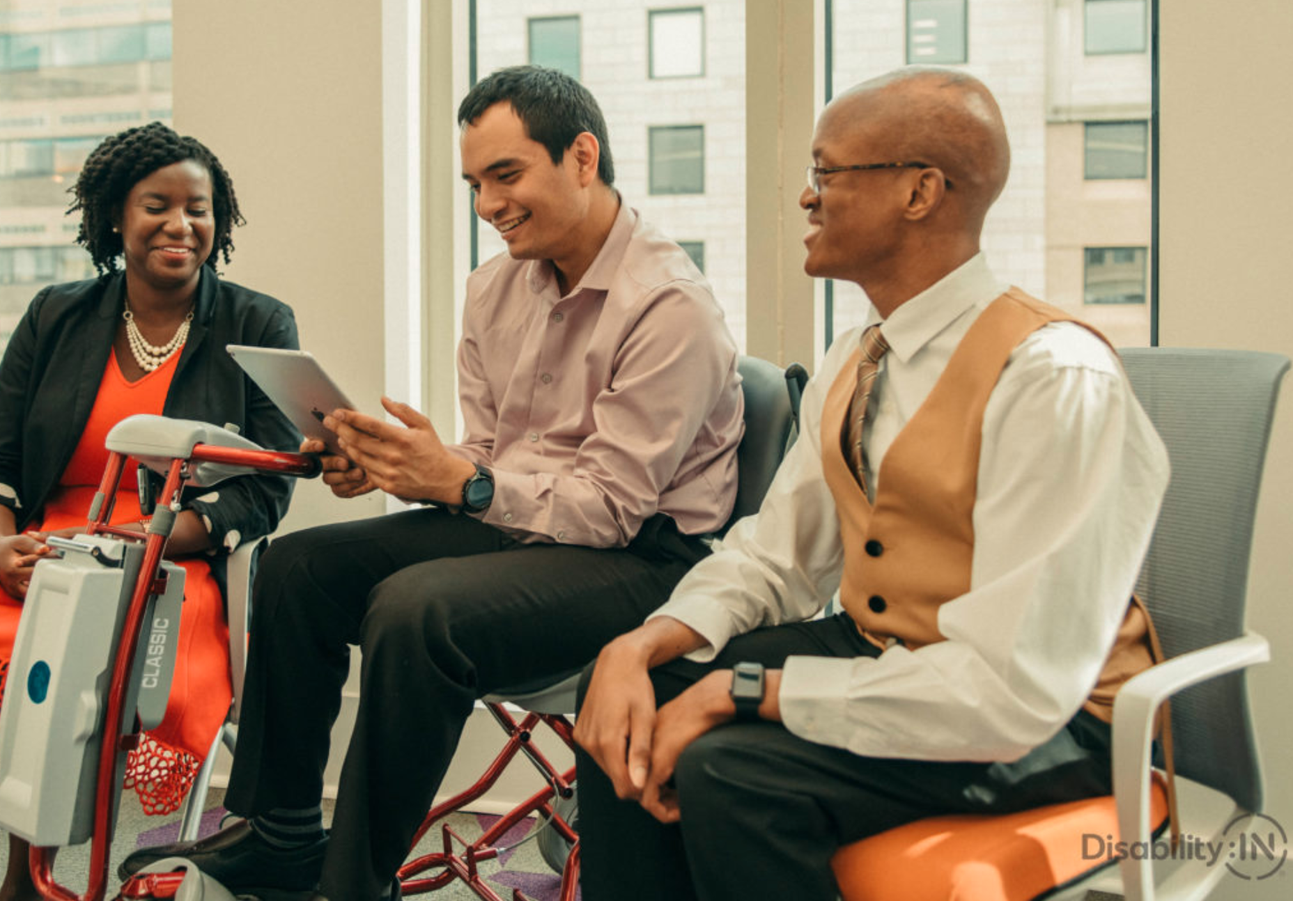 Stock photo of 3 people in a business setting, one woman, a man on a power wheelchair using an iPad, and another man on the r