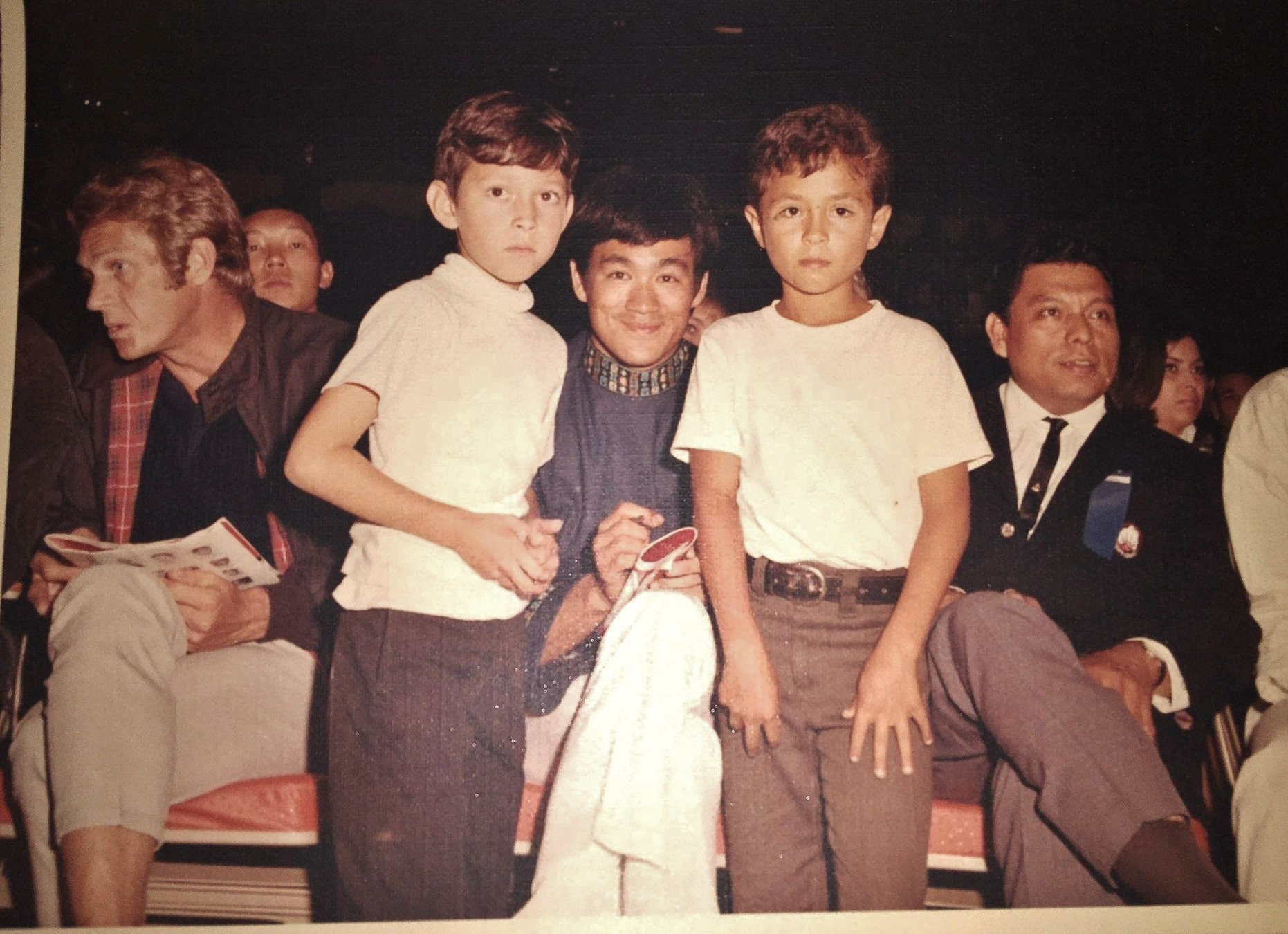Steve McQueen attentively listens to a seated companion while Bruce Lee happily signs autographs for two middle school boys