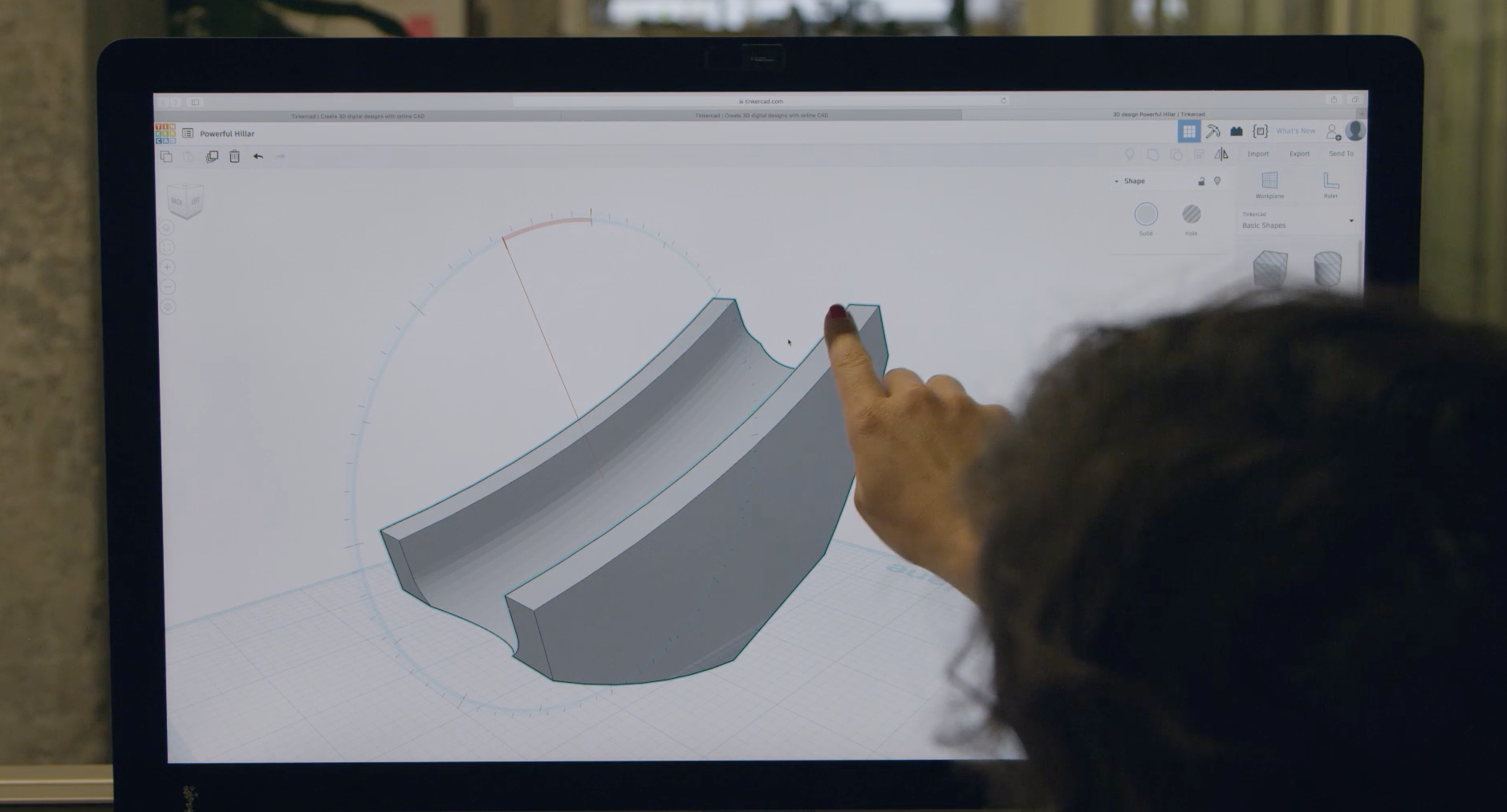 Computer screen showing a 3D model. Woman pointing to edge of 3D model.