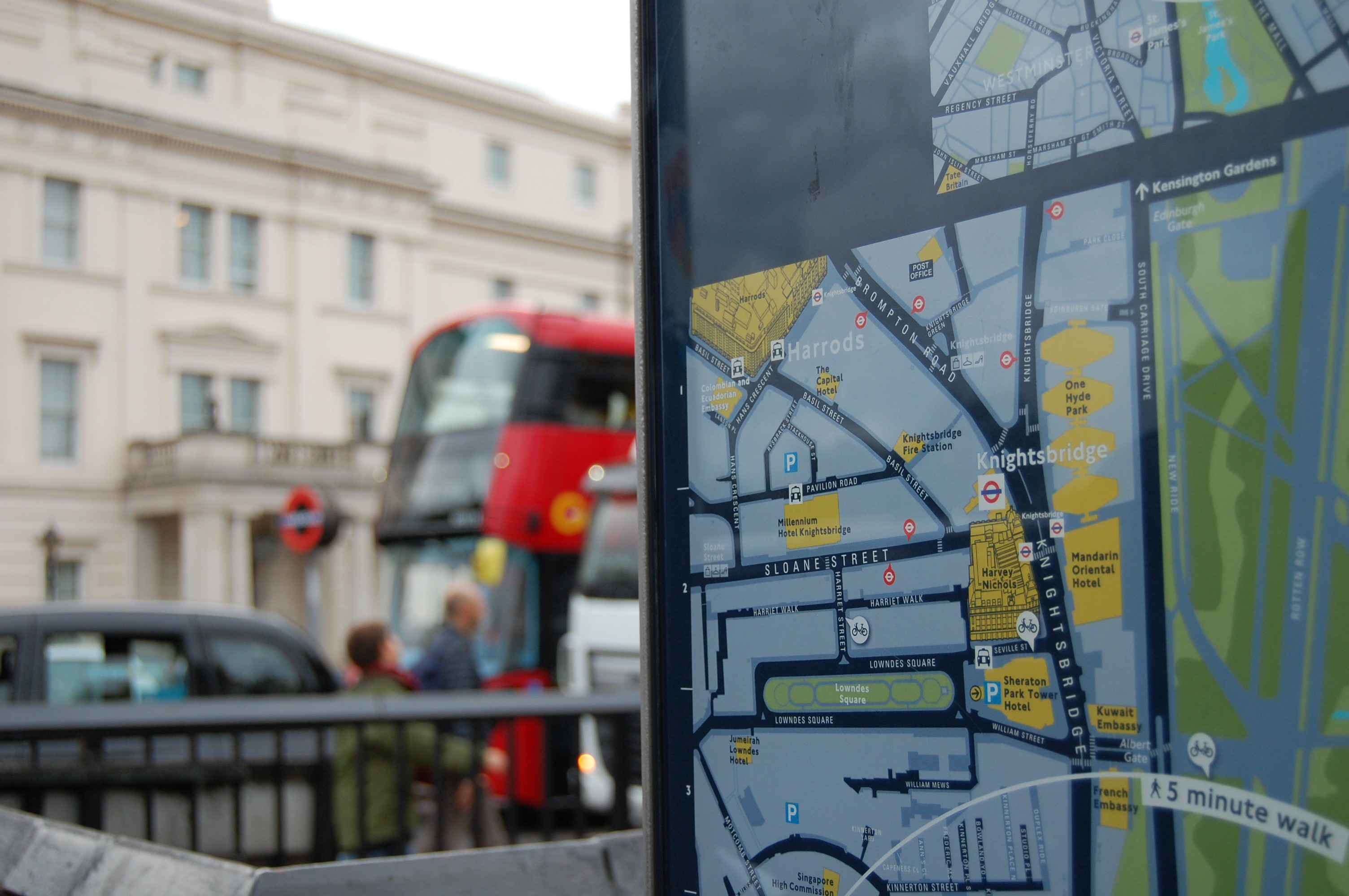 a map on a bus stop with a bus in the background