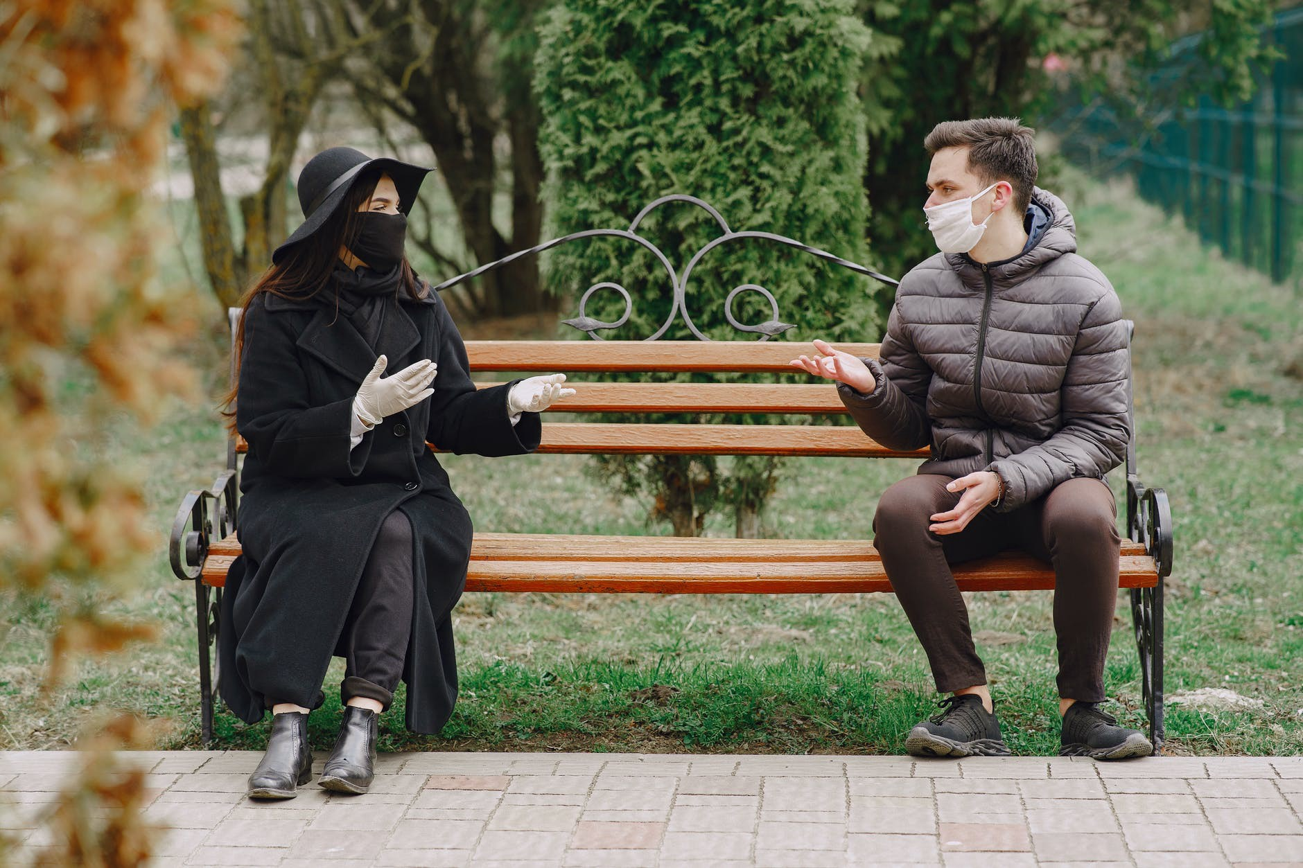 Two people wearing masks sit and converse on opposite ends of a park bench.