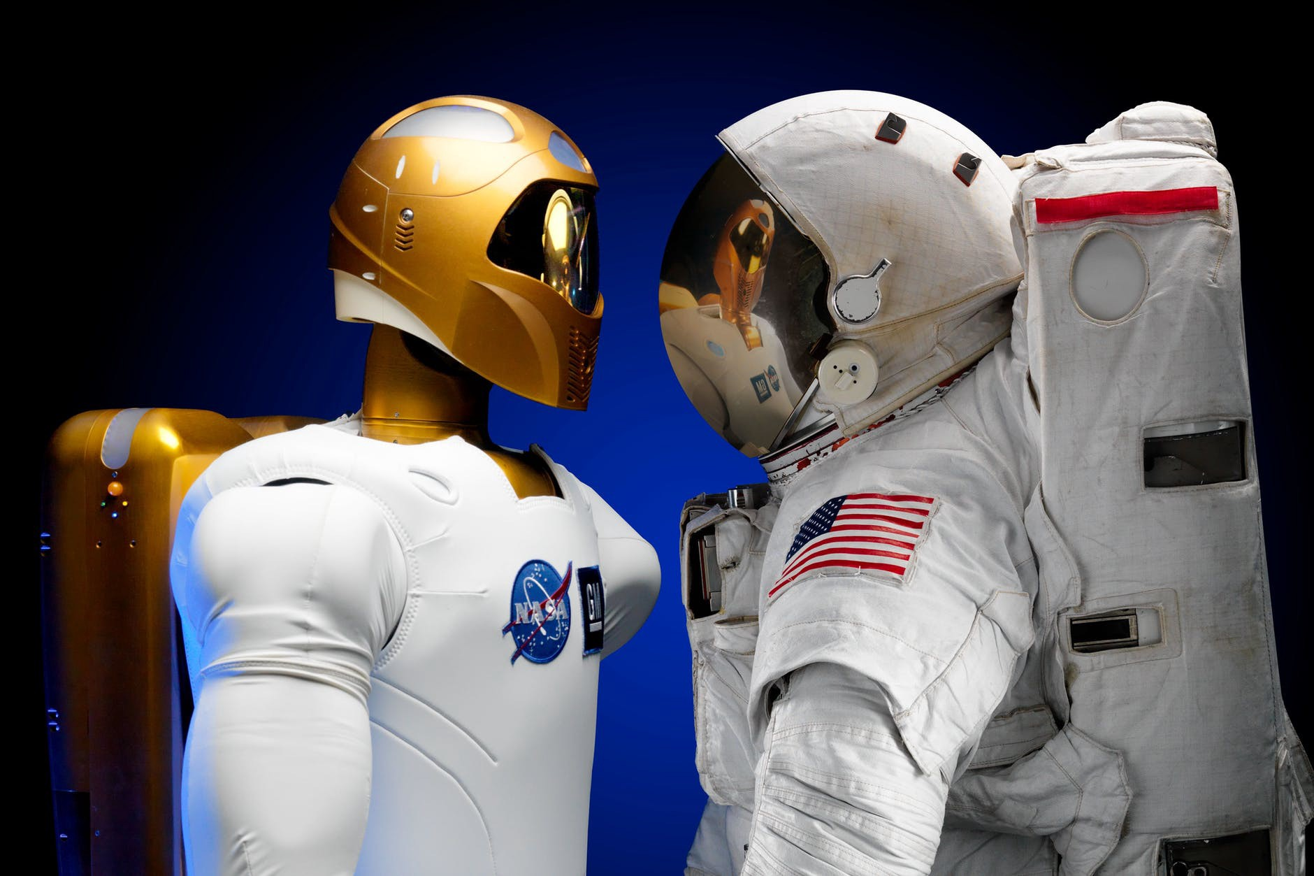 A robot and an astronaut staring at each other