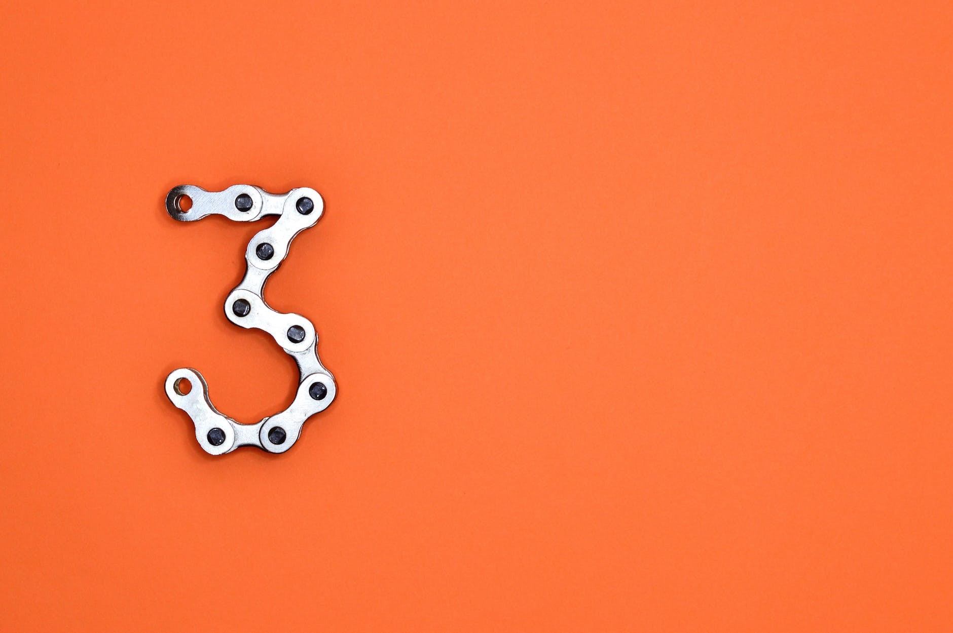 Orange background with the number three made out of hardware