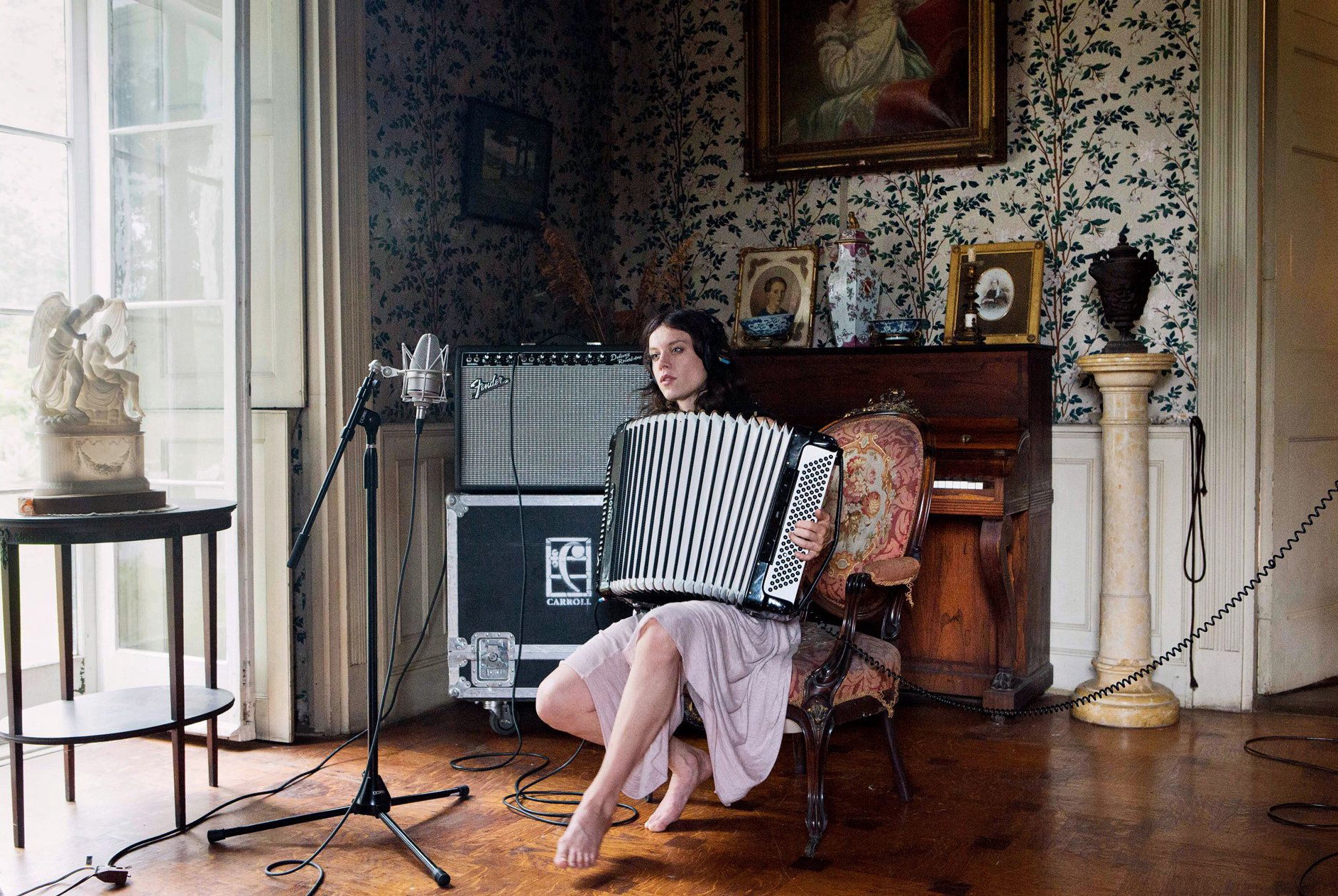A woman plays the accordion in an ornately decorated room.