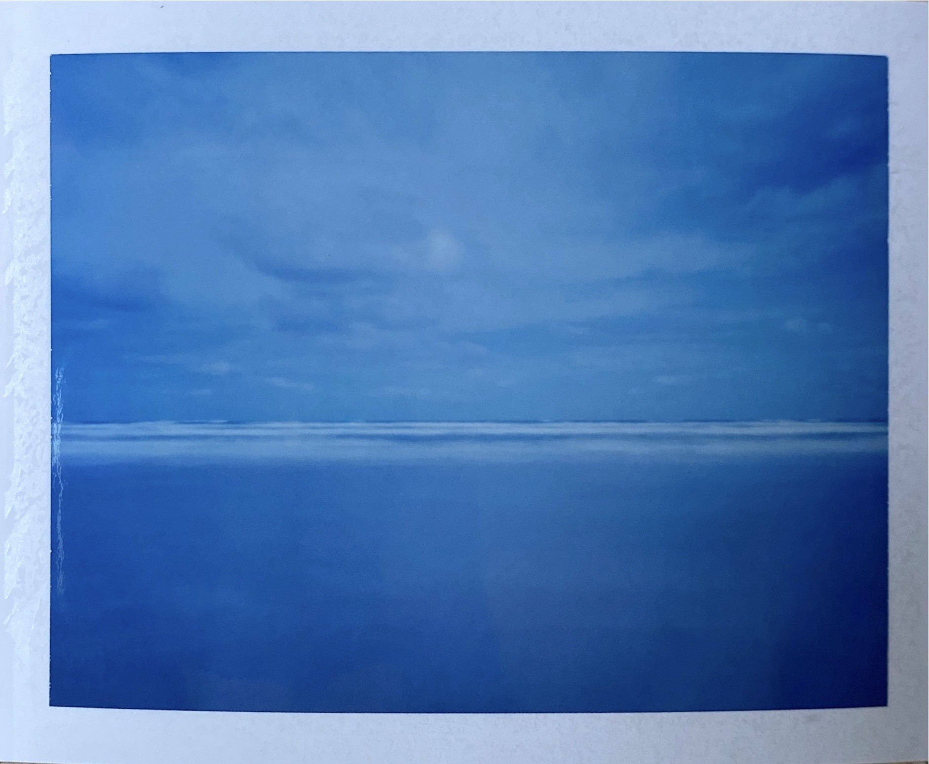 Mostly blue photograph of the ocean and sky, a calm monochromatic scene