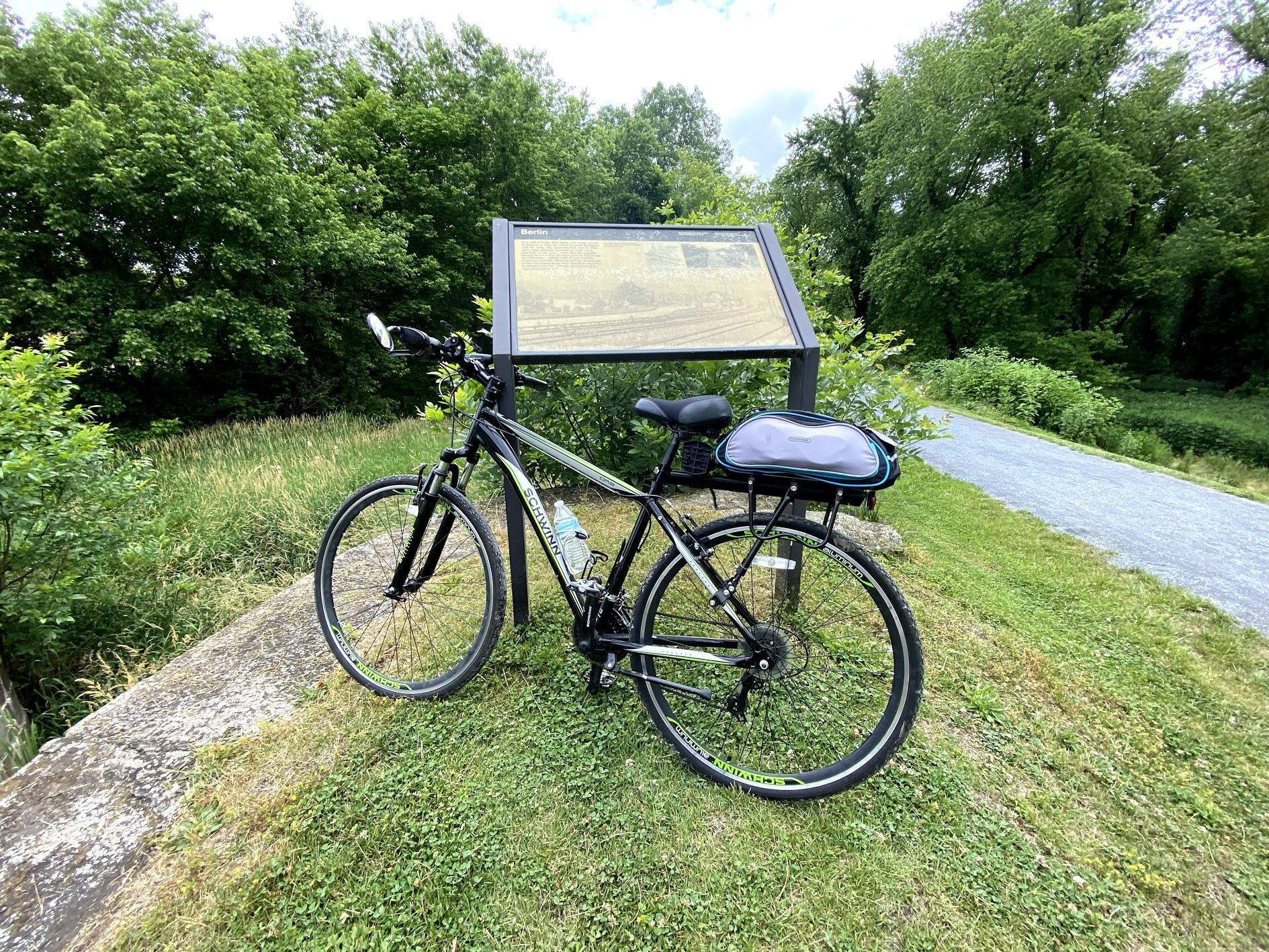 A bicycle is standing up next to a sign on a trail