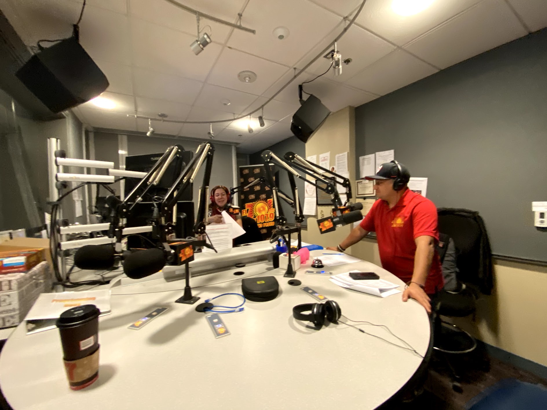 Image of a radio studio with a man and a woman at the microphones. The man is wearing a black had and a red shirt. The woman is behind equipment.