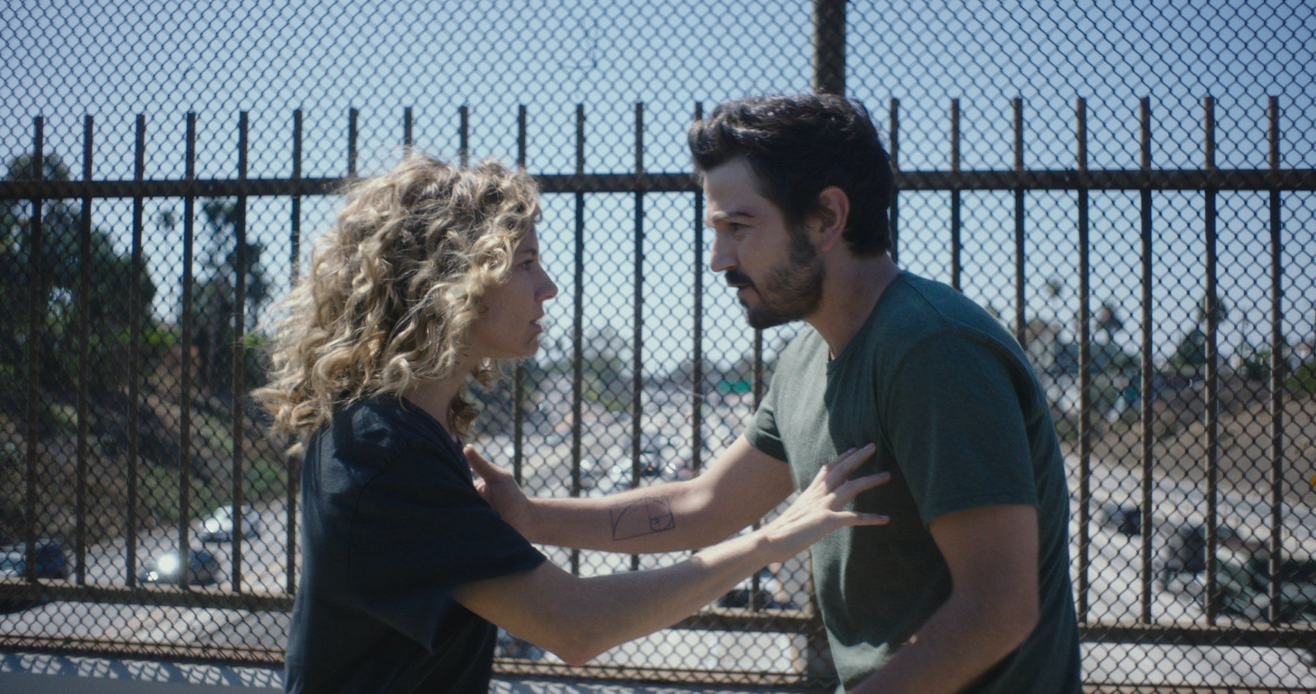 Sienna Miller and Diego Luna look at one another with intensity on a freeway overpass.