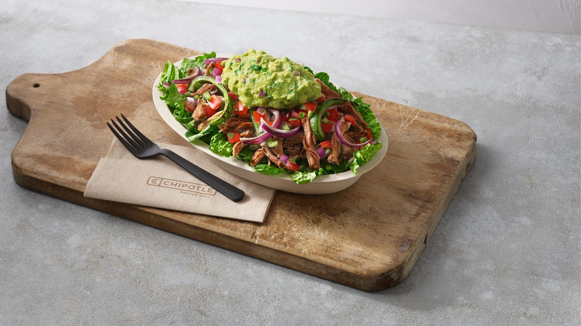 Chipotle burrito bowl on a wooden cutting board