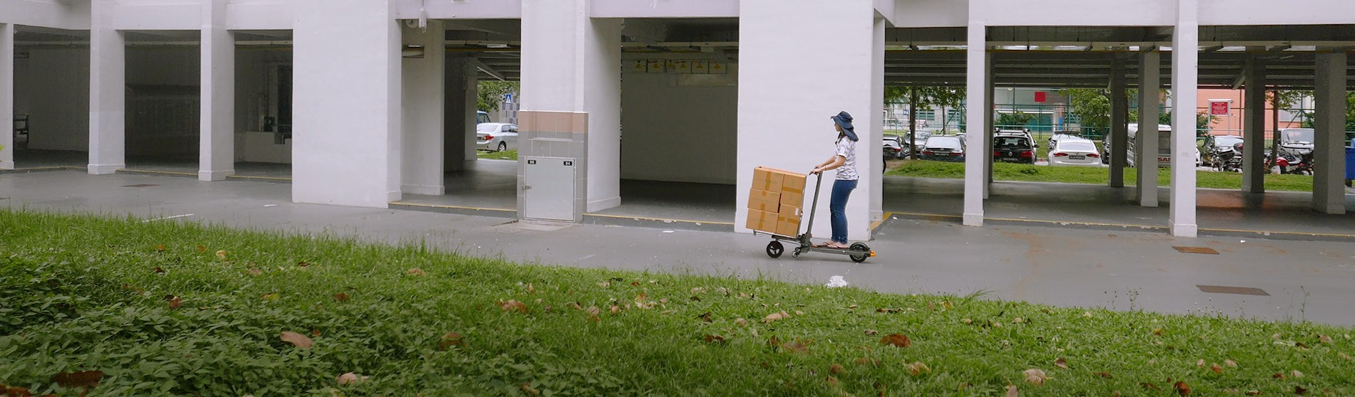 woman carrying out urban logistics delivery on cargo e-scooter