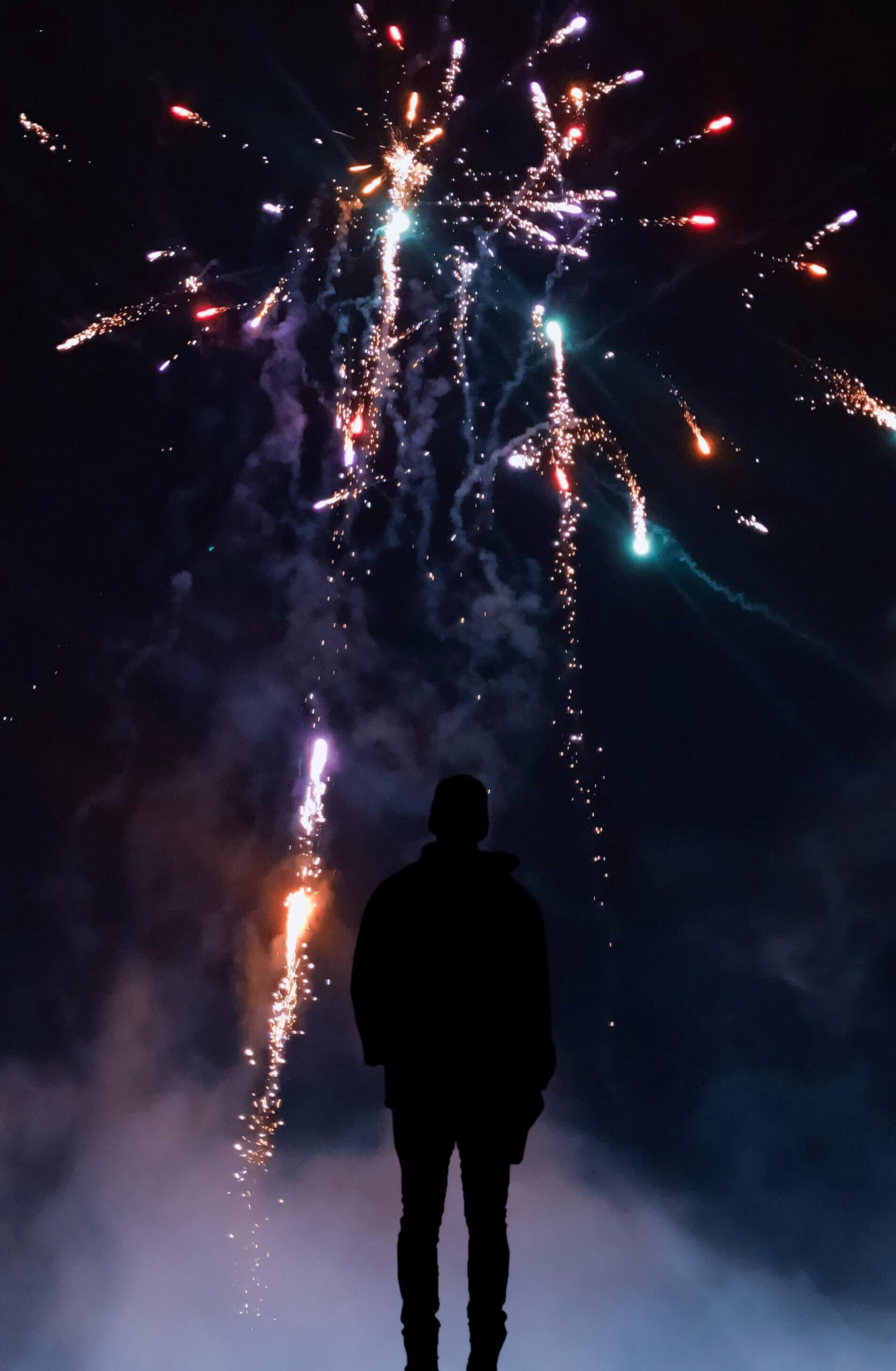 a person in silhouette watching an assortment of fireworks exploding in the dark night sky