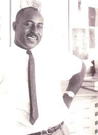 Image of African-American Male Thomas Miller. The photograph is black and white and stands with a white shirt and black necktie. He has a mustache and a smile on his face. His left arm is on his left hip and he wears a watch on his left wrist.