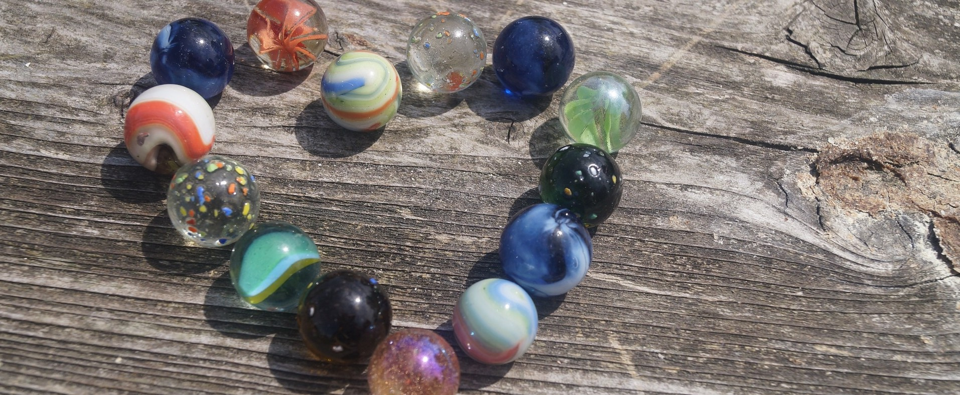 Multi-colored marbles placed in the shape of a heart on top of a wooden bench