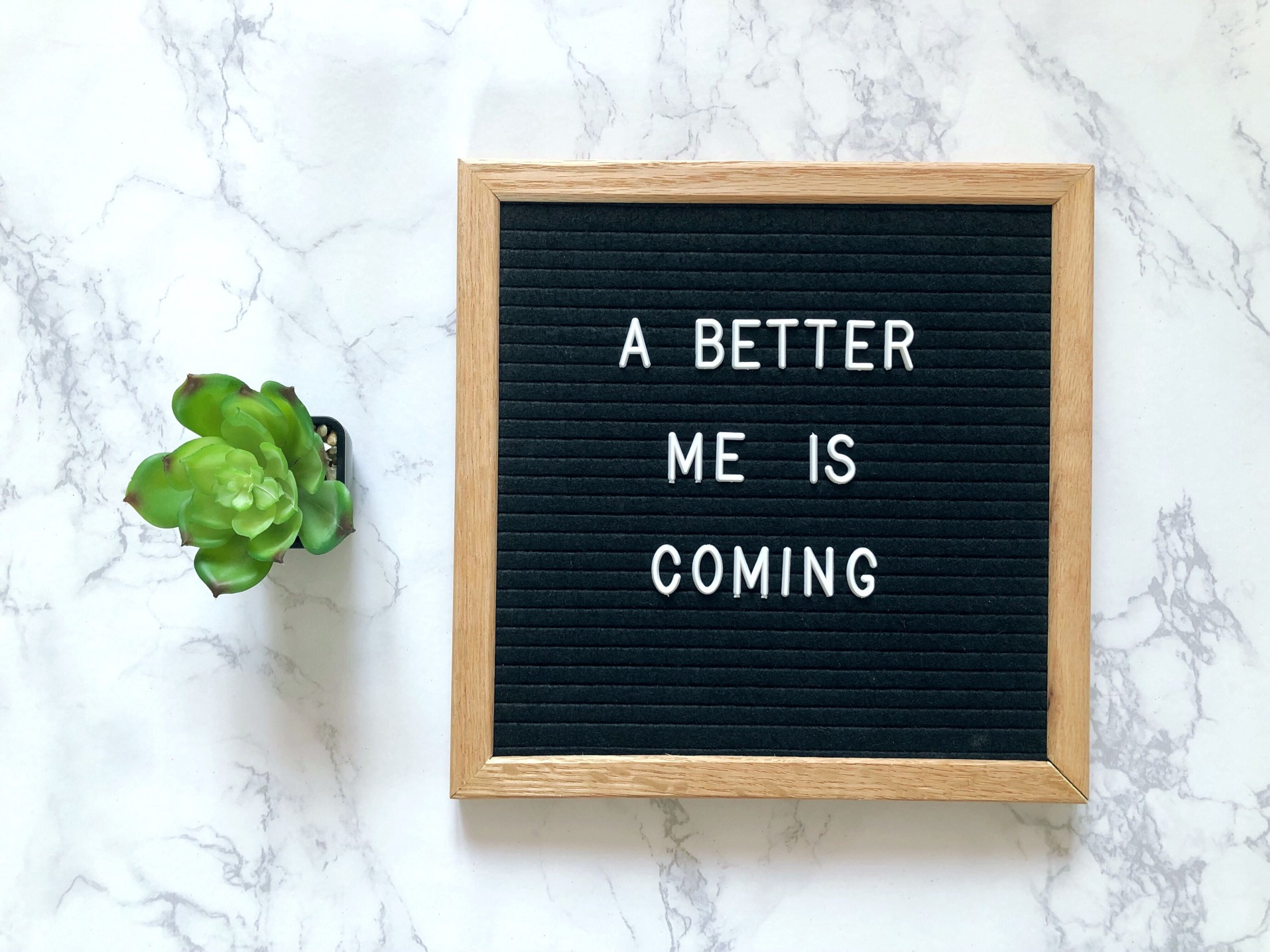A sign reading 'A better me' sits against a white background. A small plant sits beside it.