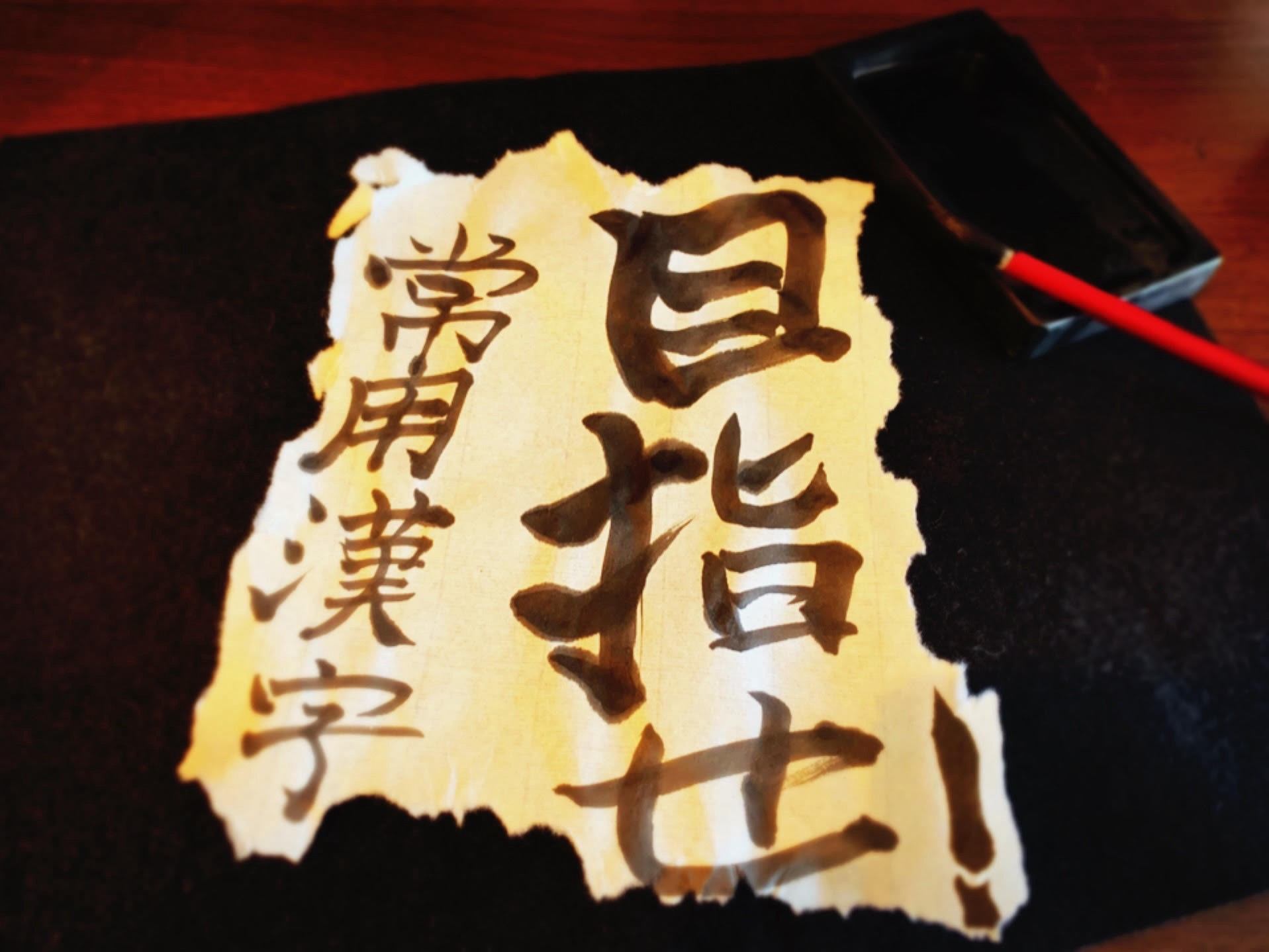 Rice paper with calligraphy written on it resting on a desk next to a traditional brush which is leaning on an ink stone.