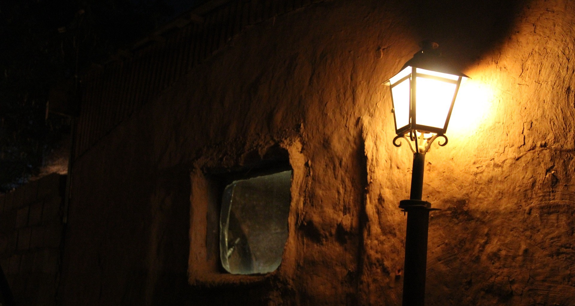 Shining old street lamp near the old wall with the window