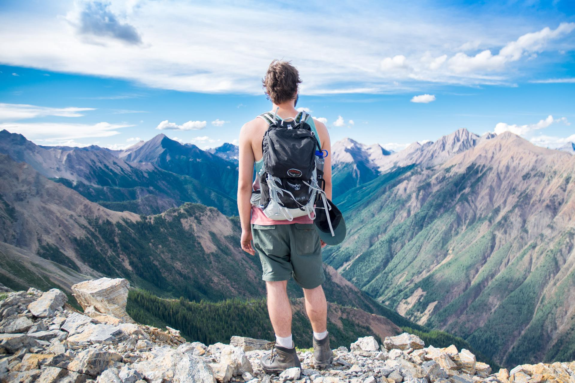 Man standing at the edge of a mountain looking at the mountain ranges and peaks around - trying to look at the big picture