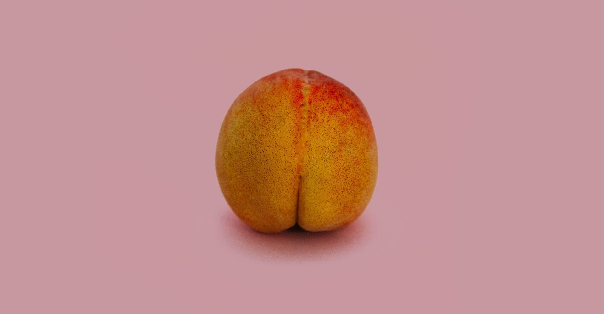A peach with a 'butt crack' on a pink background
